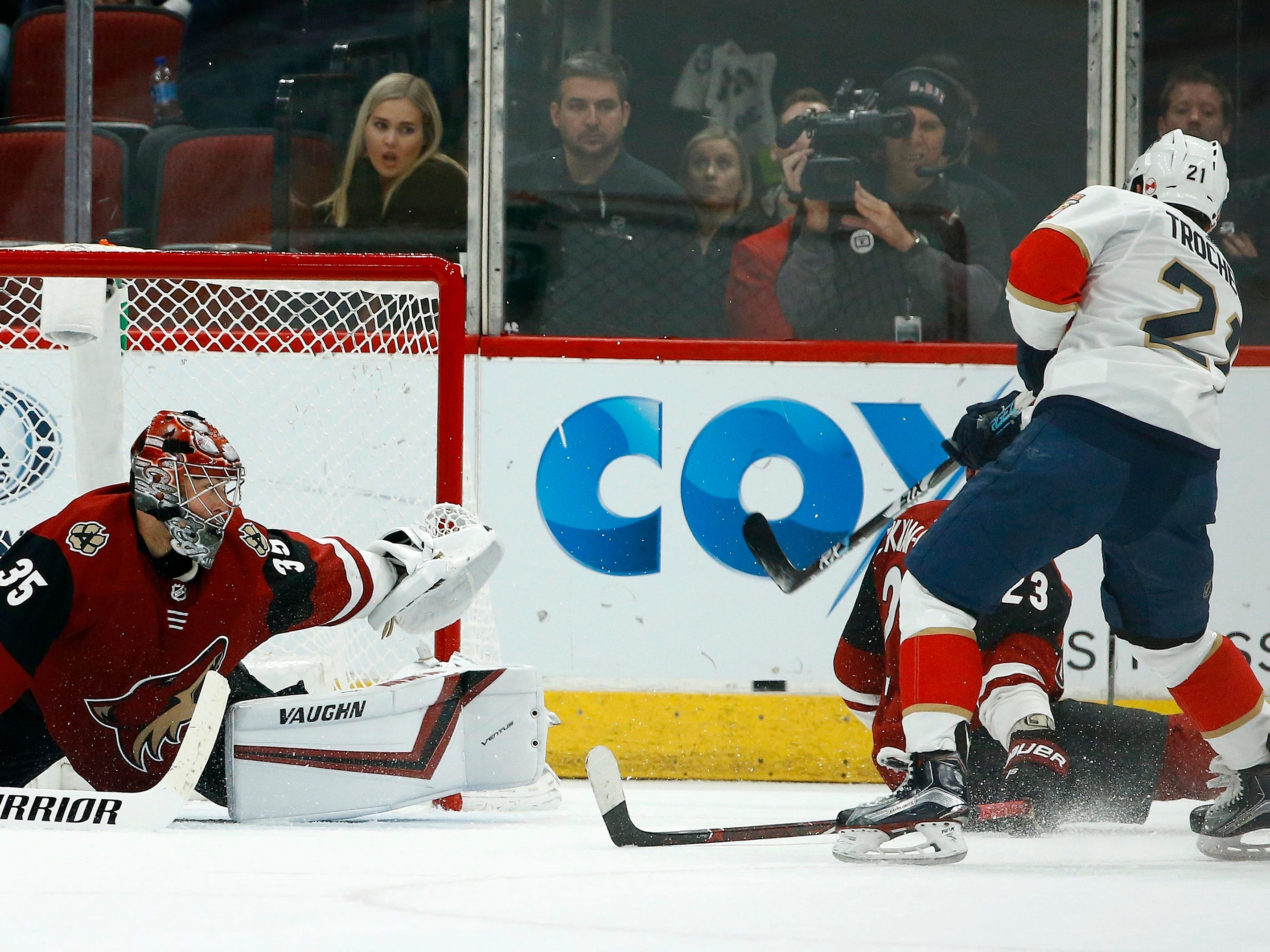Arizona Coyotes goaltender Darcy Kuemper (35) gets some help from defenseman Oliver Ekman-Larsson (23), stopping the puck on a shot by Florida Panthers center Vincent Trocheck (21) during overtime in an NHL hockey game Tuesday, Feb. 26, 2019, in Glendale, Ariz. The Coyotes won 4-3 in a shootout.