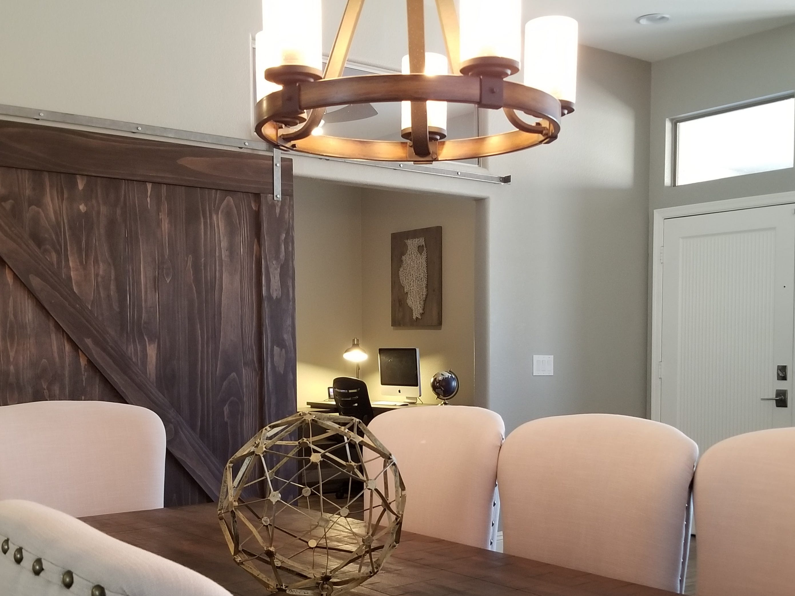 Staggered walnut plank flooring and gray-toned walls set the color palette for the home. Simple yet elegant furnishings complete the living and dining rooms. A bay window overlooking the porch area of the home filters light throughout both rooms.