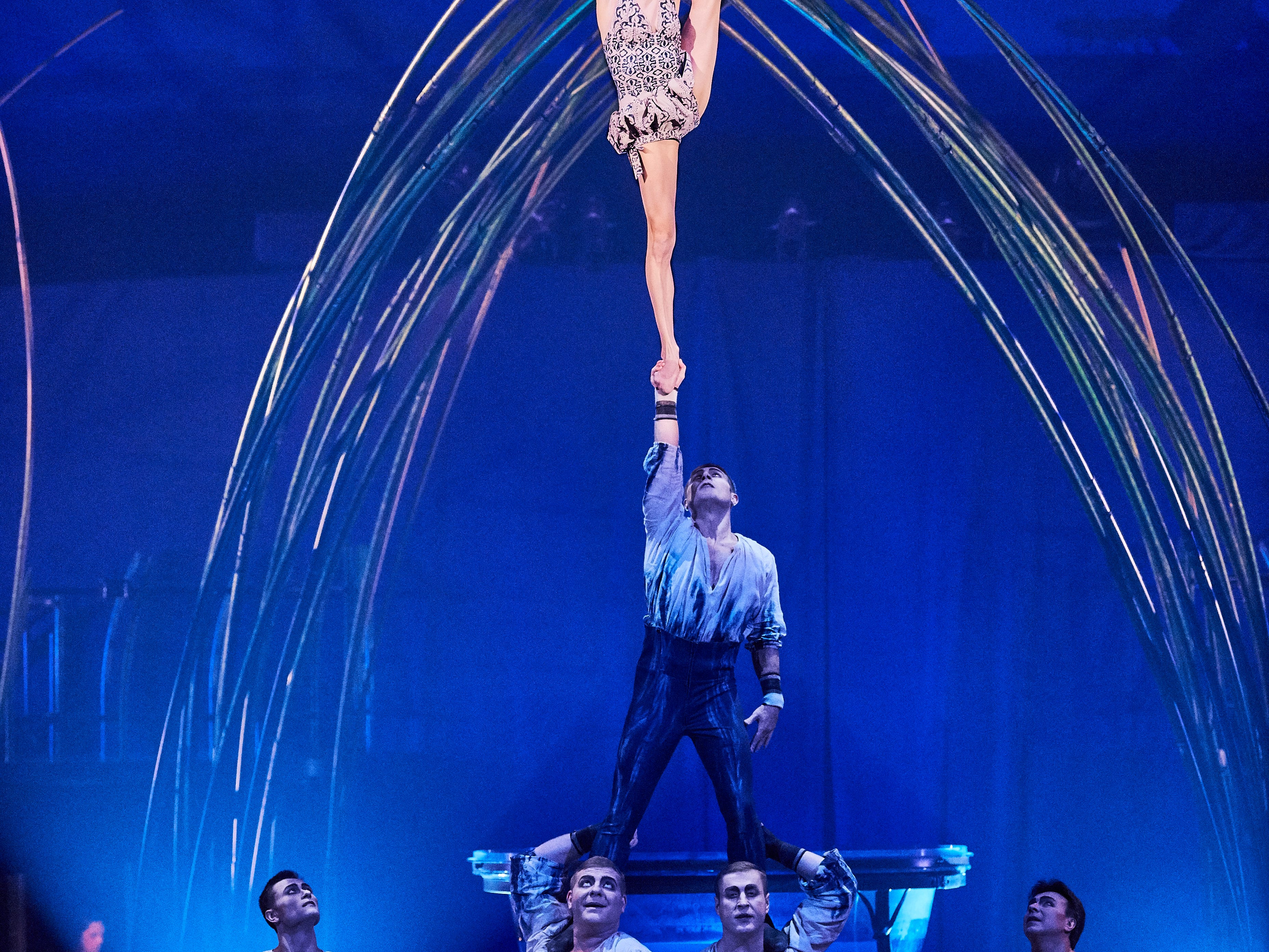 Cast members perform an acrobatic celebration where the porters interlock their arms and hands to create platforms, from which the flyers take-off and perform aerial tricks in Cirque Du Soleil.