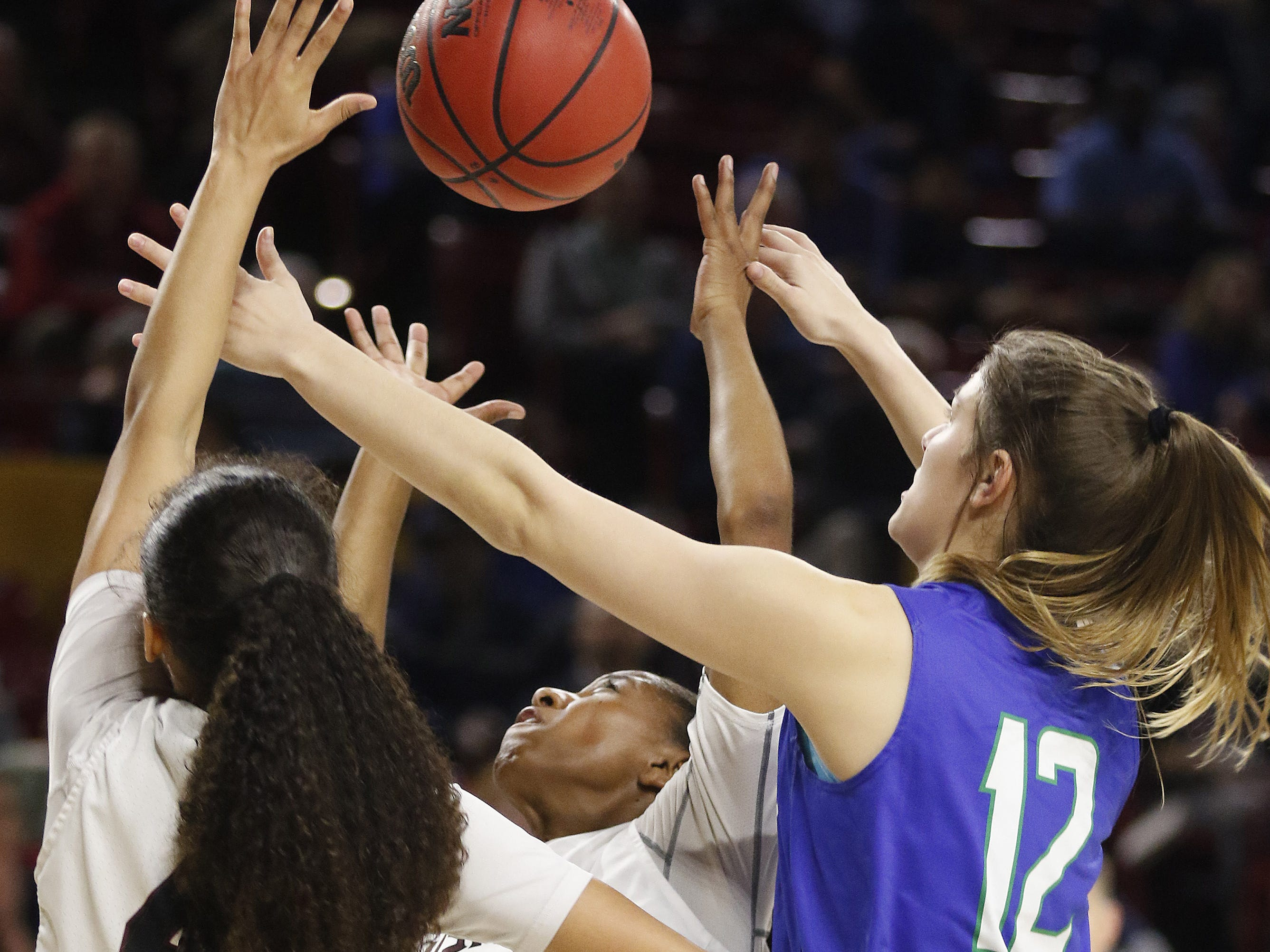 Xavier's Addie PutnamÊ(12) battles for a rebound with Hamilton's Amyah Reaves (4) and Victoria Davis (10) during the 6A Girls State Championship at Wells Fargo Arena in Tempe Tuesday, Feb 26, 2019.
