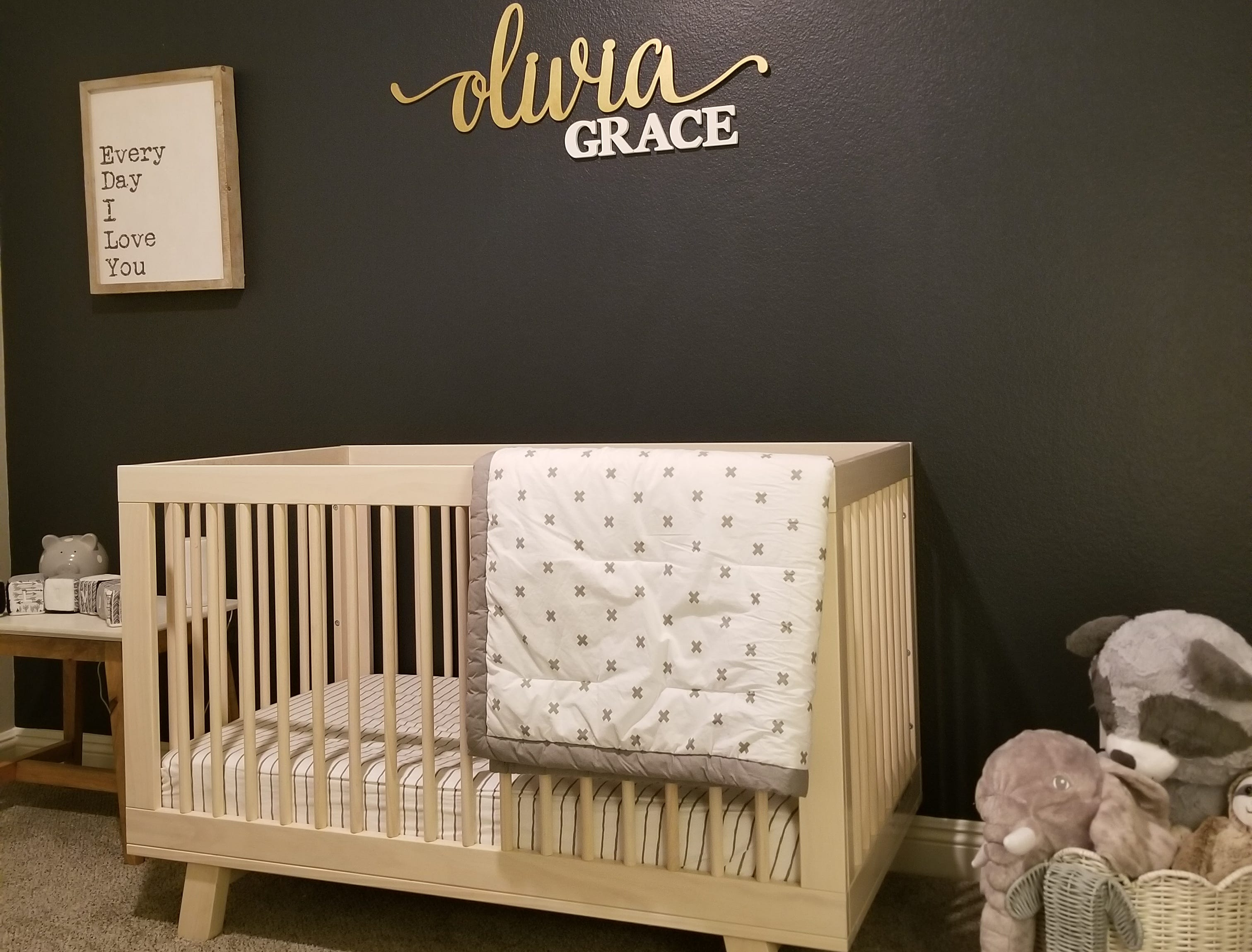 The nursery for their daughter, Olivia Grace, is one of sophistication. While lending to the color scheme throughout the couple's home, a midnight blue accent wall with lettering elegantly announcing its treasured occupant frames the modern box crib.  Whimsical accruements provide a magical respite for this blessed child.