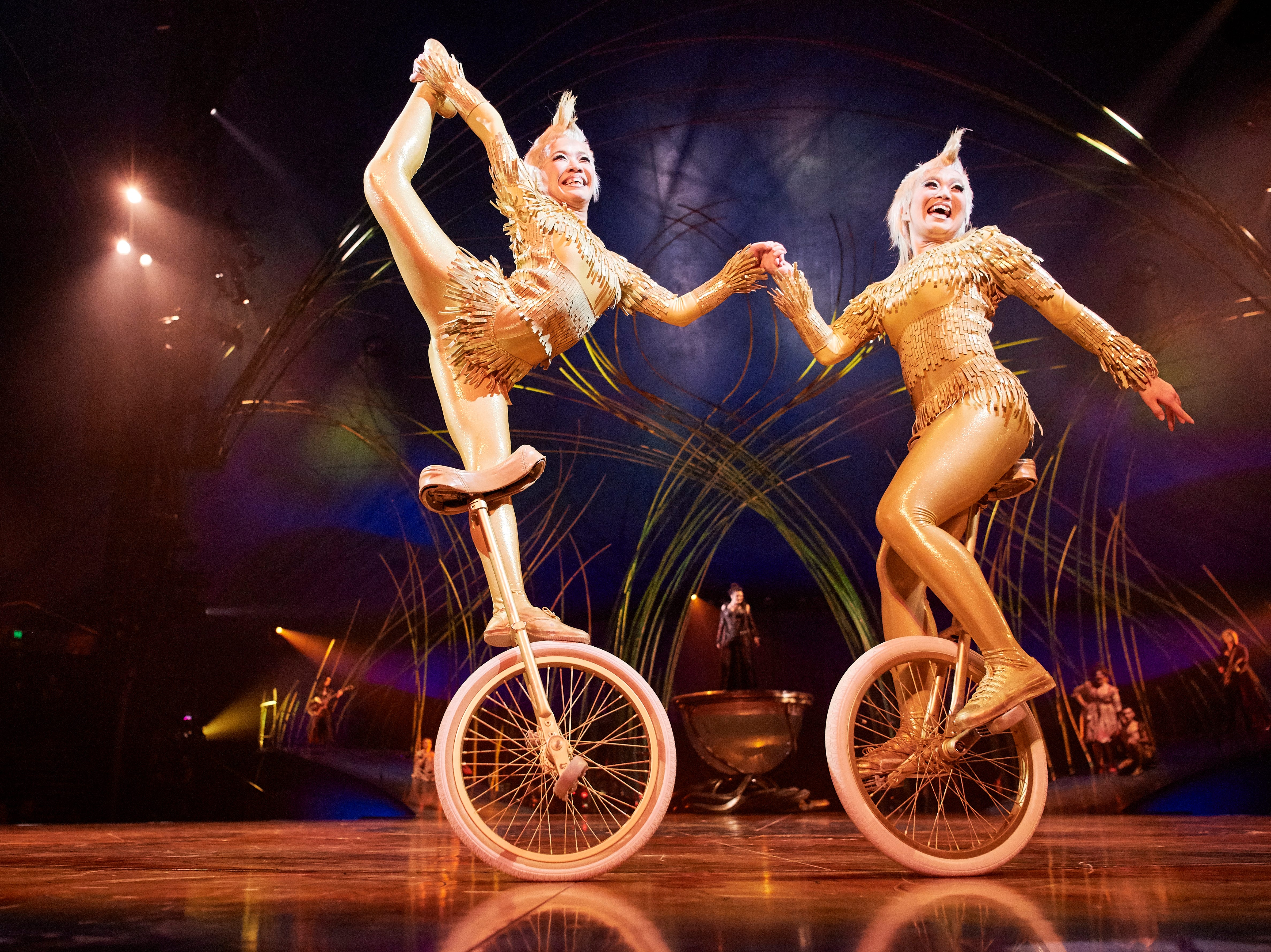 Two artists enter on unicycles wearing hoop skirts of gold, weaving in and out of each other's paths like the wind as they joyfully pirouette, dance and thrill the pageant participants.