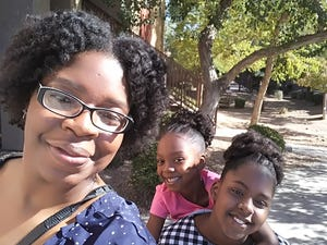 Rakesha Hill, of Mesa, pictured with two of her children, received help from the Lend a Hand program to pay off an auto title loan.