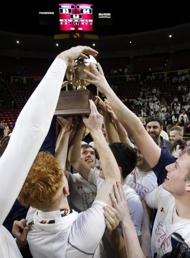 Pinnacle players hold up the Gold Ball after their 83-64 win over Chaparral in the 6A Boys State Championship at Wells Fargo Arena in Tempe Tuesday, Feb 26, 2019.