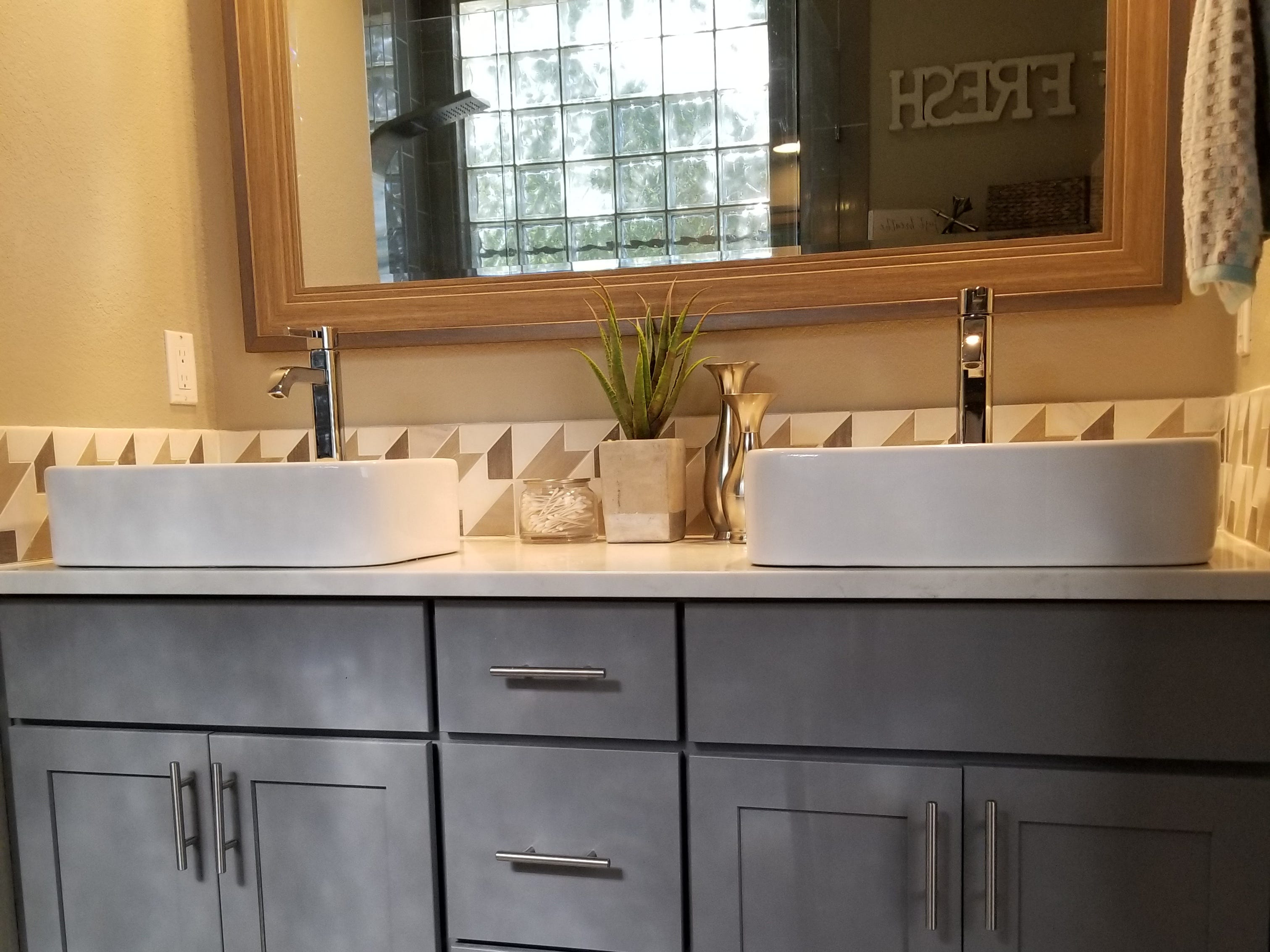 A complete tear-down was worth the end result, which is nothing short of spectacular.  Light grey subway tile set vertically with lighter grout lines replaced a garden tub. Product niches situated below the glass block, and positioned behind a bench seat add depth and interest to the design. A blend of 1-inch tiles in whites and greys define the shower floor. As if the shower head purchased online with multiple functions and separate hand-held nozzle doesn't seal the deal, the installation of clear glass doors deliver the final punch of sophistication and exquisite style. Kris, the sweat equity star of the home, removed and replaced the original builder double vanity with one sporting the grey palette resplendent throughout the home. Both sinks share a large rectangular mirror.  Industrial shelving and a metal chair now occupy the space assigned the original builder shower.