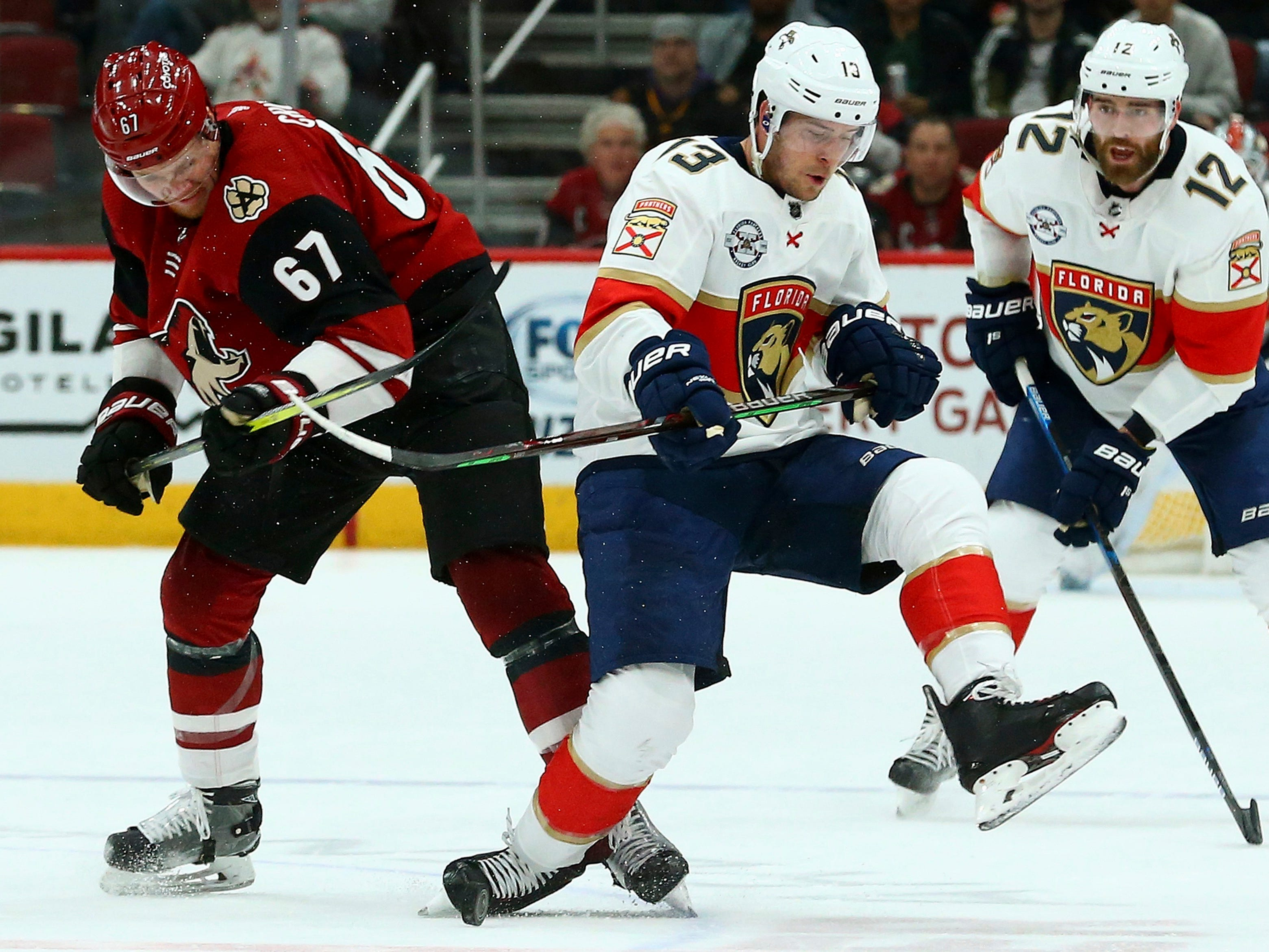 Arizona Coyotes left wing Lawson Crouse (67) competes with Florida Panthers defenseman Mark Pysyk (13) for the puck as Panthers defenseman Ian McCoshen (12) watches during the first period of an NHL hockey game Tuesday, Feb. 26, 2019, in Glendale, Ariz.