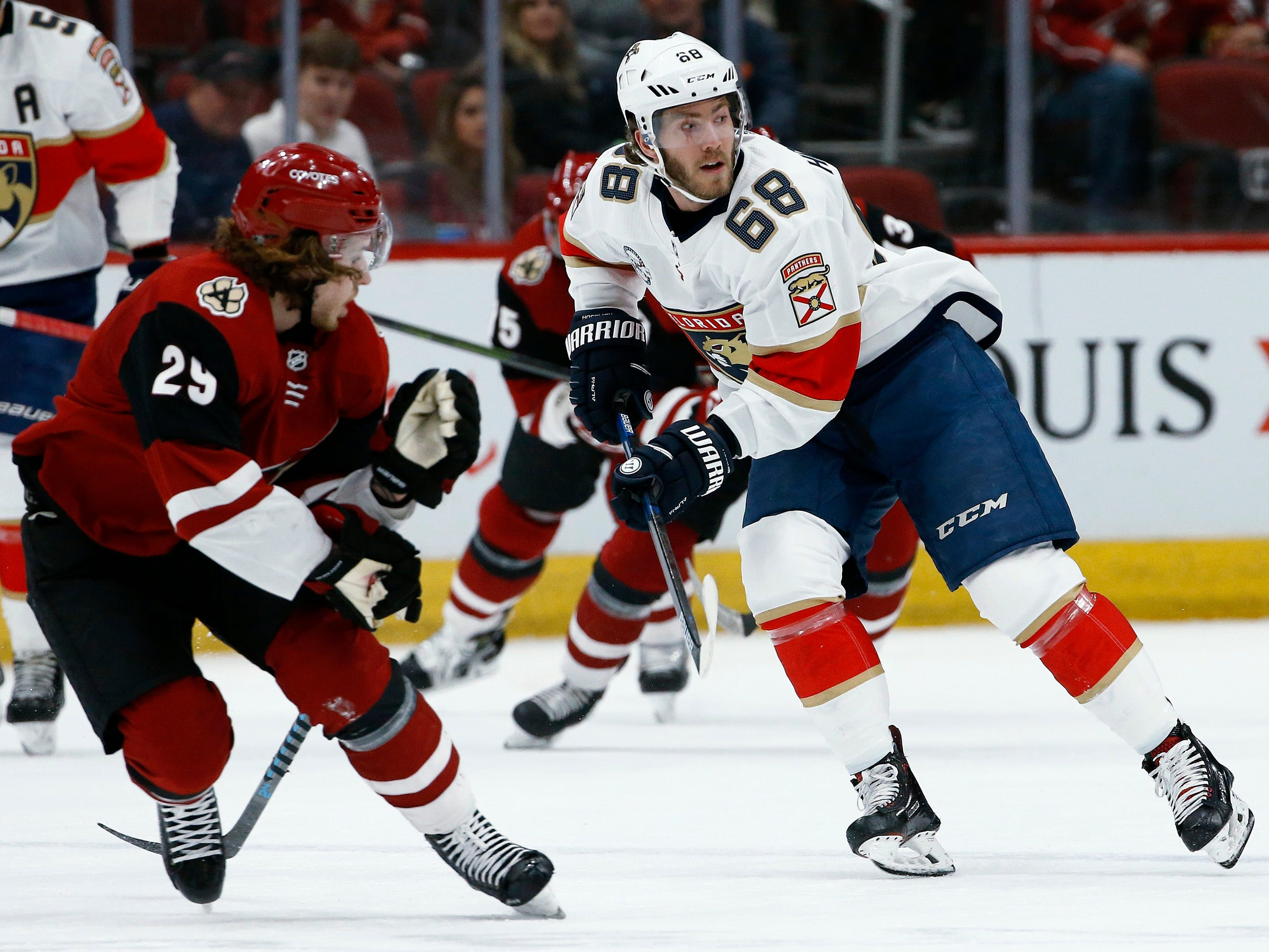 Florida Panthers left wing Mike Hoffman (68) passes the puck in front of Arizona Coyotes right wing Mario Kempe (29) during the first period of an NHL hockey game Tuesday, Feb. 26, 2019, in Glendale, Ariz.
