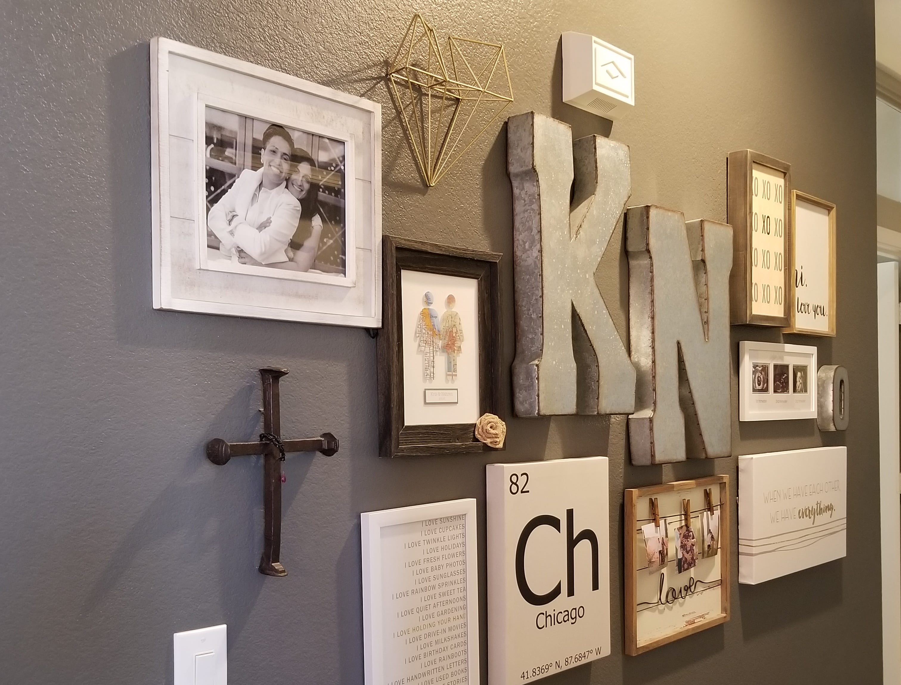 "The hallway leading to the master suite creatively reflects the couple's journey: a wedding photo along with ultrasound and maternity glimpses of Olivia Grace, represented by a smaller letter ""O"" on a wall painted dark grey is a stunning tribute to their love story."