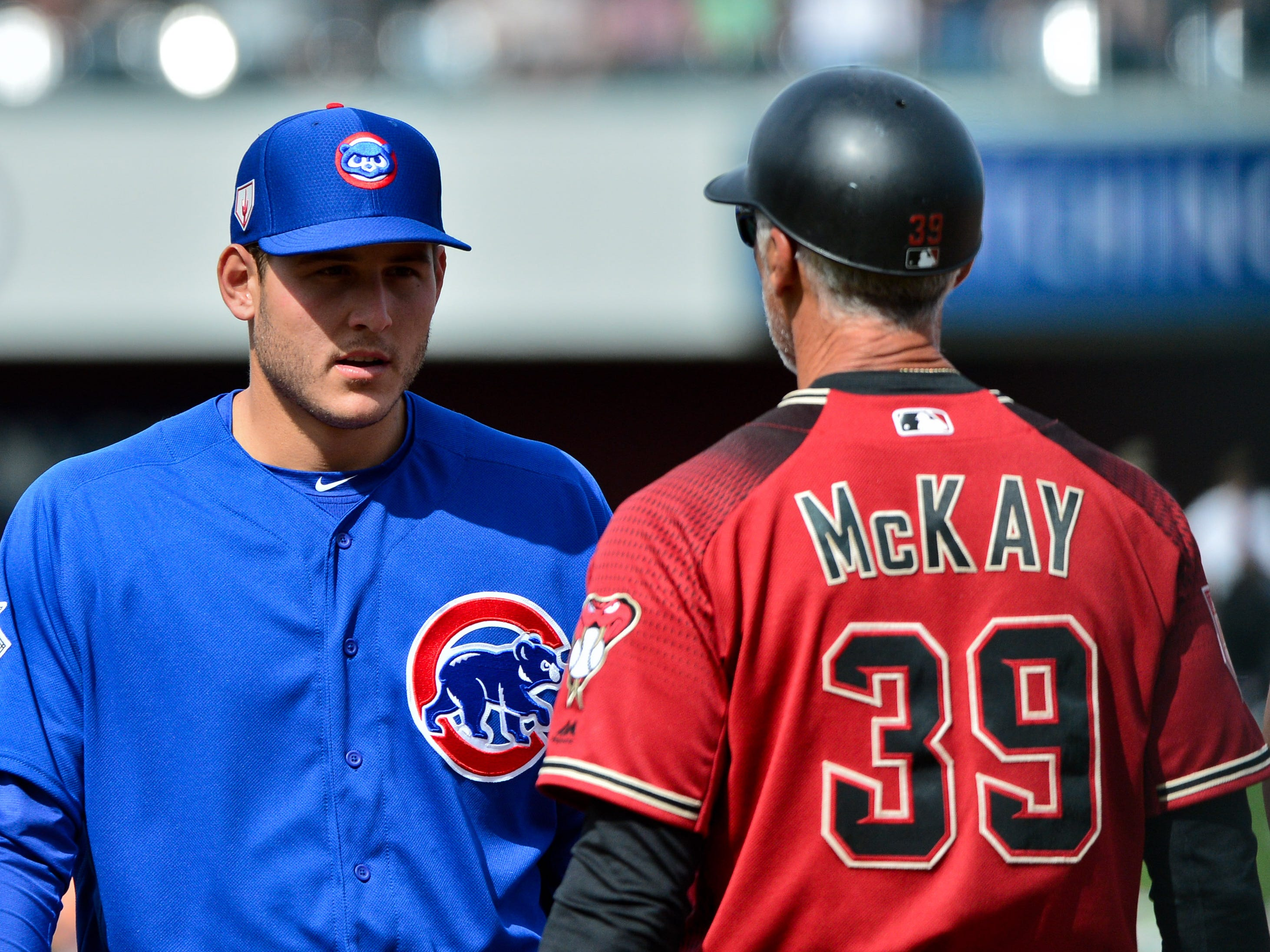 Feb 26, 2019: Chicago Cubs first baseman Anthony Rizzo (44) talks with Arizona Diamondbacks first base coach Dave McKay (39) during a break in play in the second inning at Sloan Park.