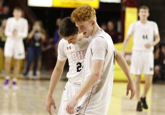 Pinnacle seniors Trent Brown (24) and Nico Mannion walk off the court for the last time together during their 83-64 win win over Chaparral during the 6A Boys State Championship at Wells Fargo Arena in Tempe Tuesday, Feb 26, 2019.