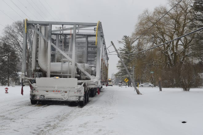 An oversized load pulled down communication lines while traveling down Michigan Road on Wednesday.