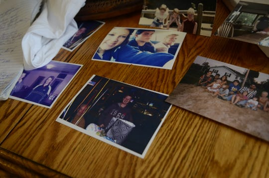 Photos of Kevin Anderson with friends and family members sit on the kitchen table of his mother's home.