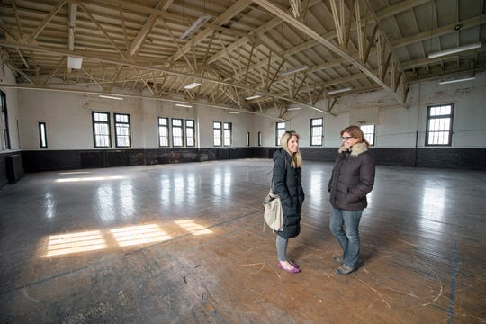 Co-founders of Kidspace Jessica Brubaker, left, and Jennifer Tansey stand inside the second-floor gym inside the former York Armory building on North George Street in York. The room will retain the original trusses and open space.