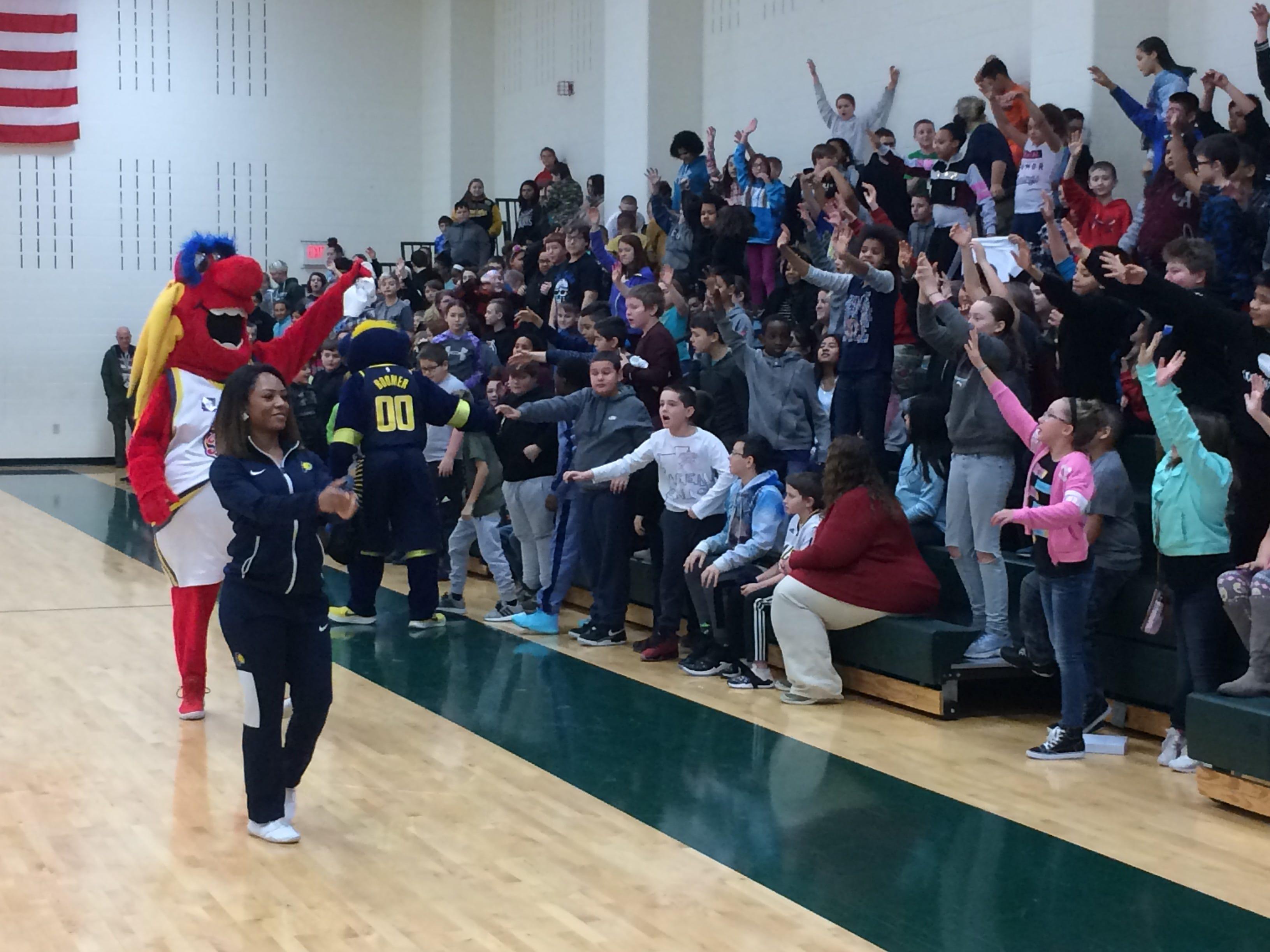 Pacemate Shania, Freddy Fever and Boomer distribute T-shirts to Dennis Intermediate School students Wednesday.