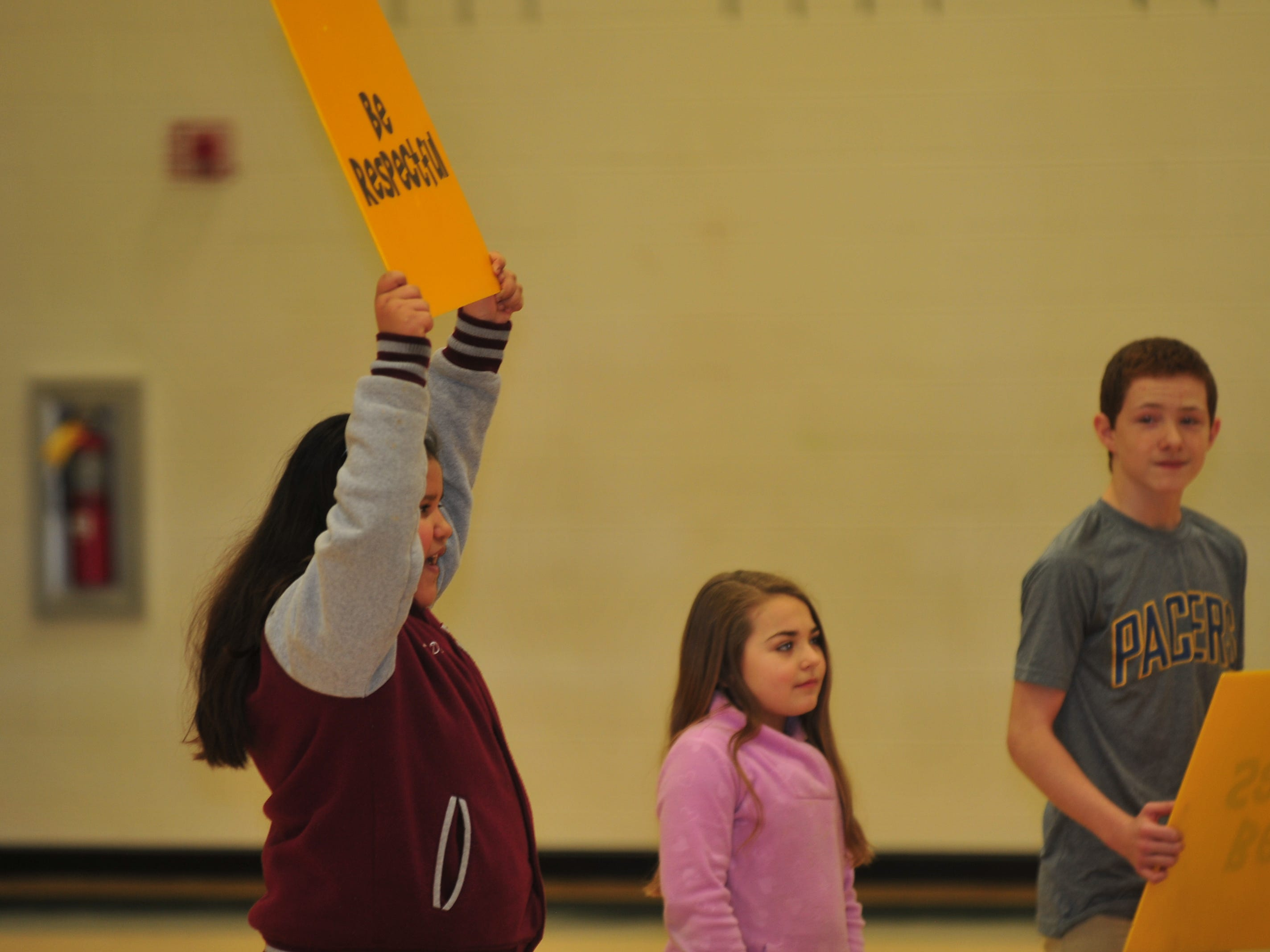 A volunteer holds up a sign urging students to be respectful during Boomer's program at Dennis Intermediate School.