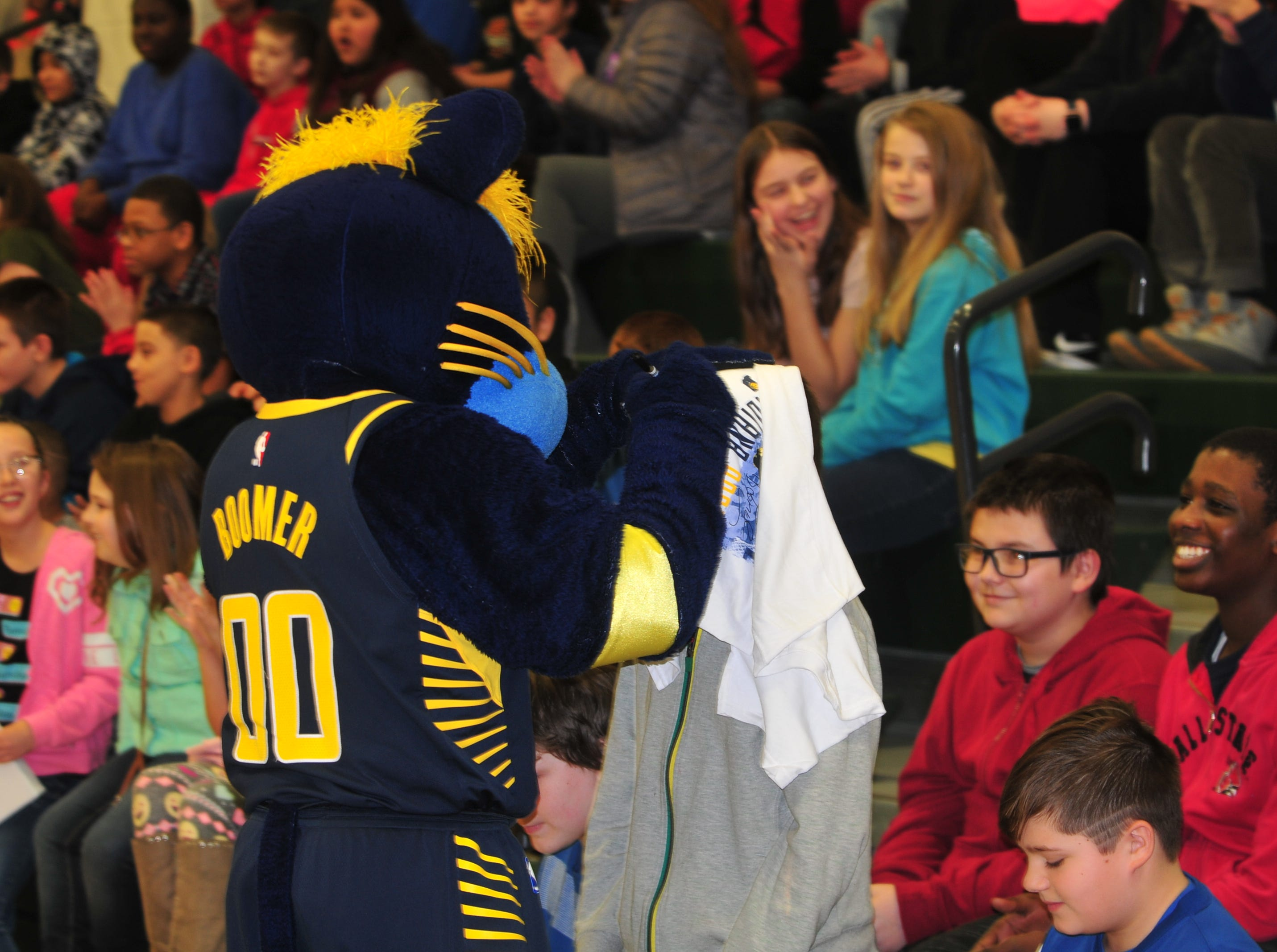 Boomer uses a student's head as a solid surface to autograph a T-shirt near the end of Wednesday's program in Dennis Intermediate School.