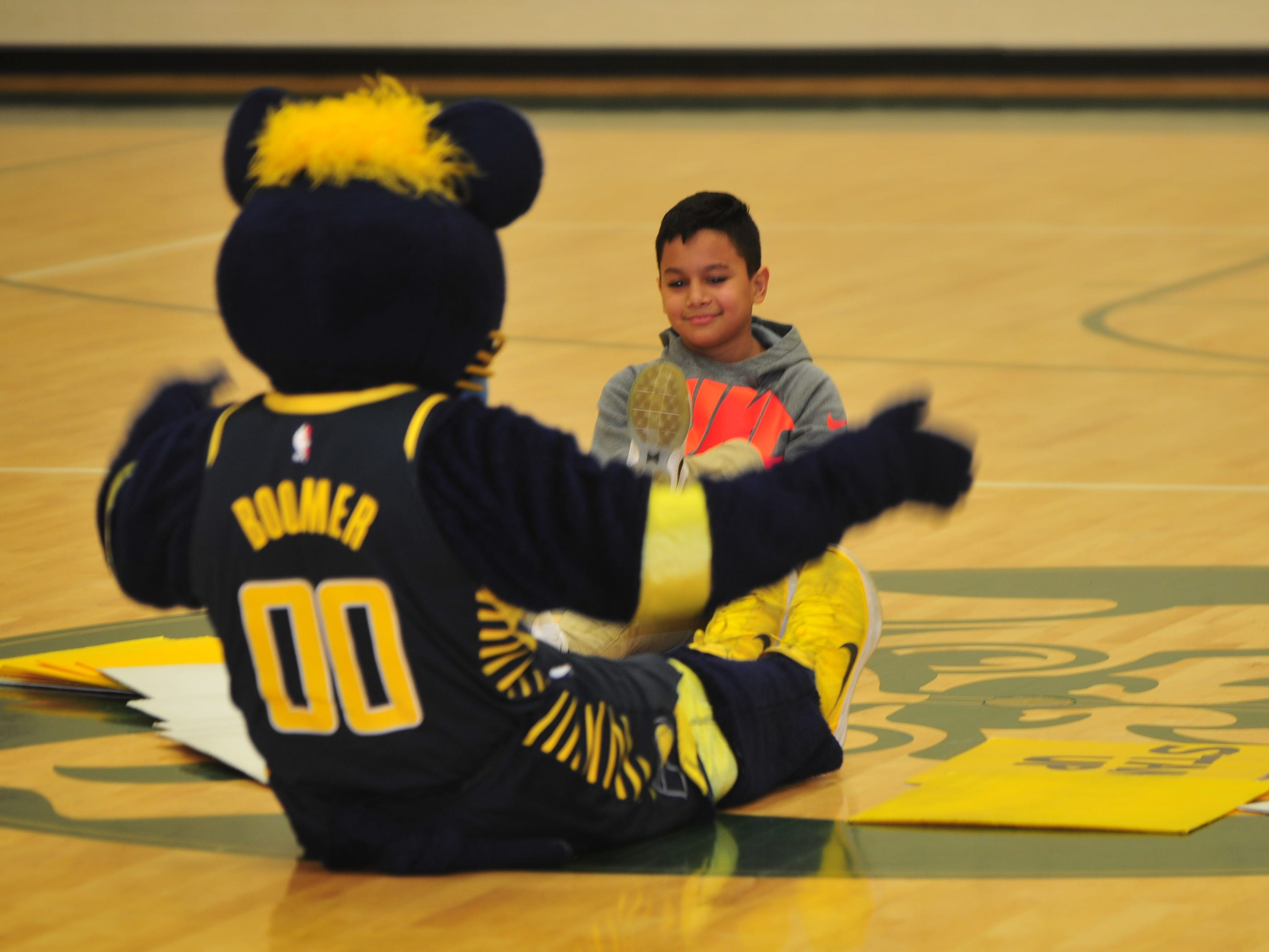 Boomer and a volunteer exercise on the floor as Boomer encourages Dennis Intermediate School students to maintain physical fitness.