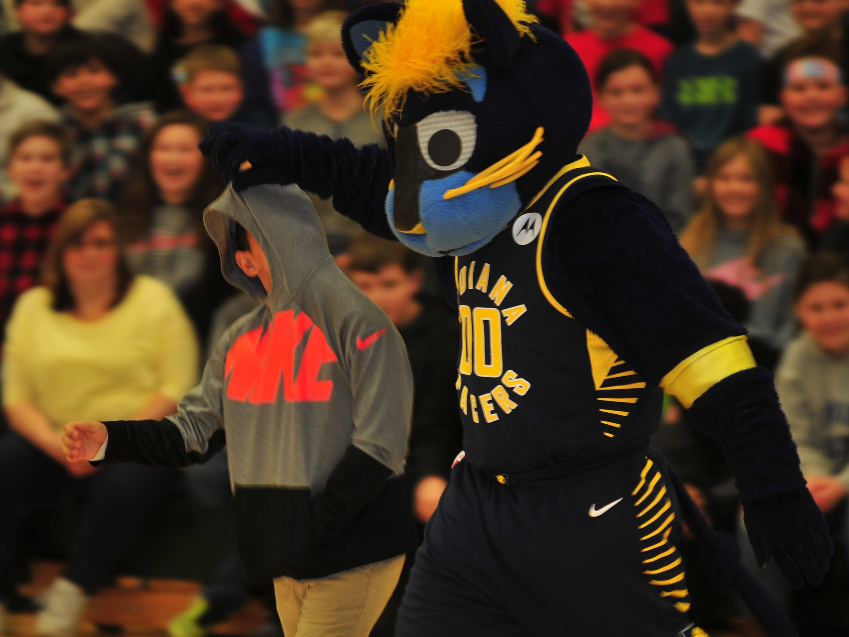Boomer, mascot for the NBA's Indiana Pacers, brings a volunteer onto the basketball court Wednesday in Dennis Intermediate School.
