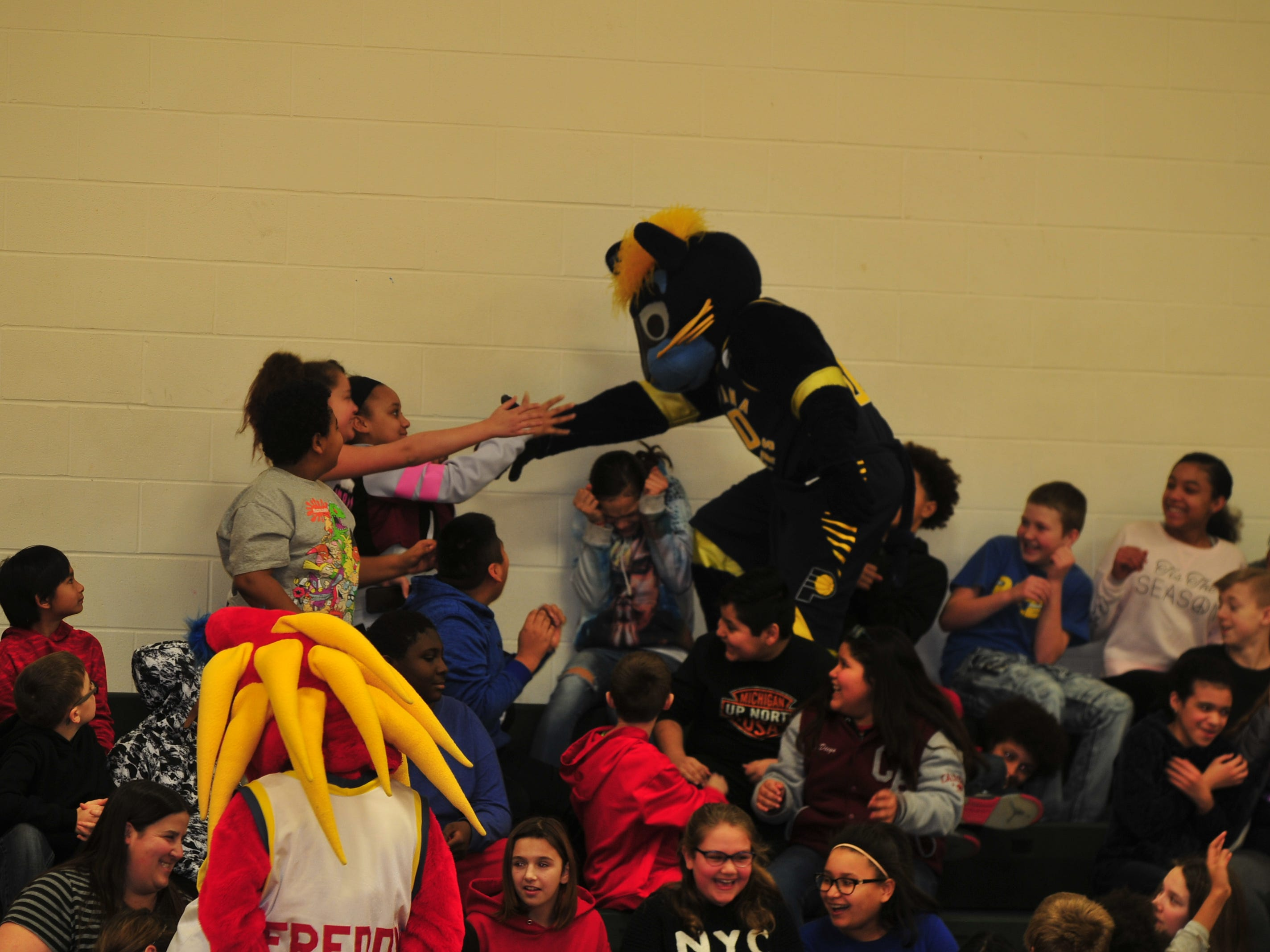 Boomer, mascot for the NBA's Indiana Pacers, greets Dennis Intermediate School students Wednesday.
