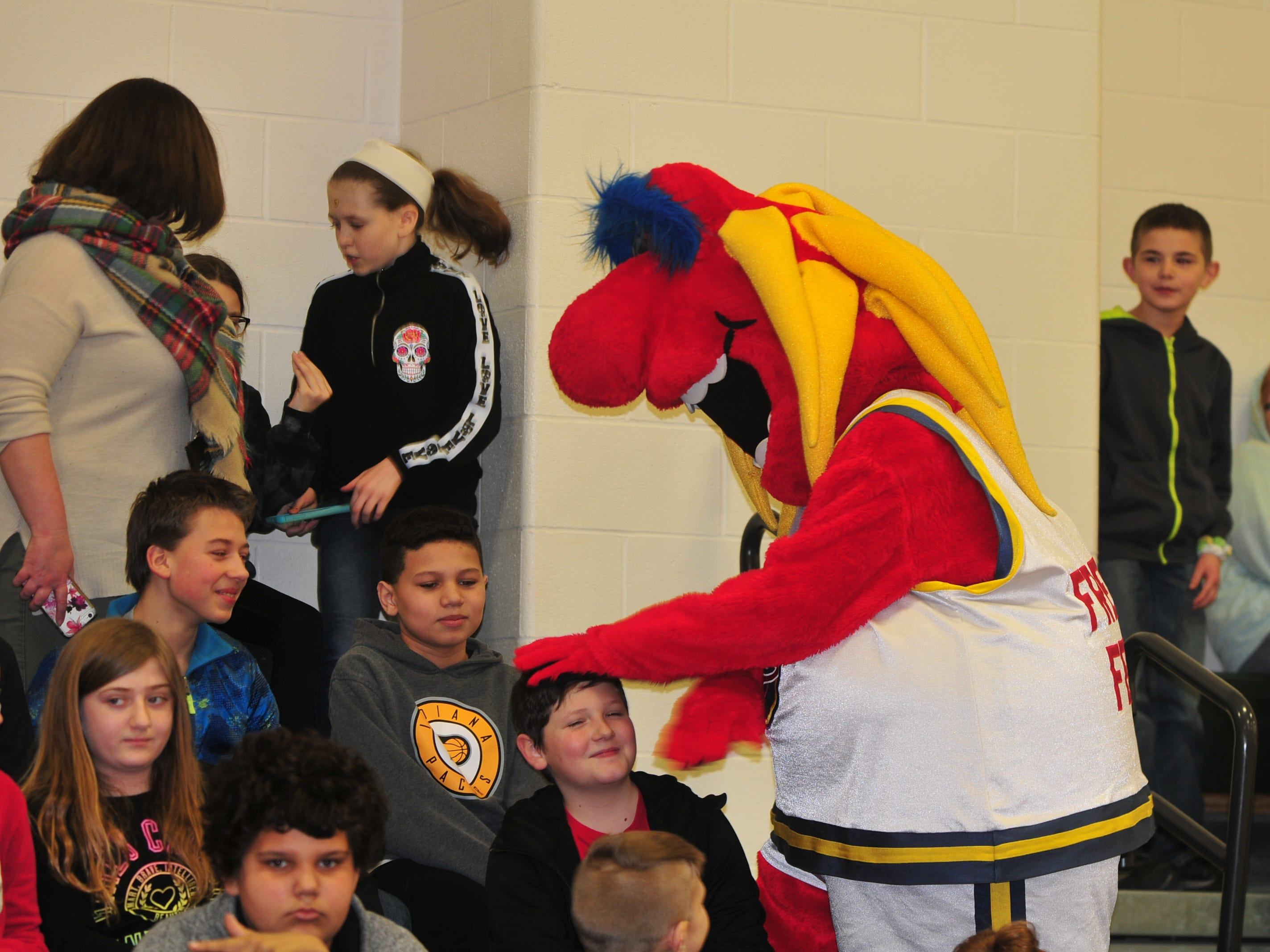 Freddy Fever, mascot for the WNBA's Indiana Fever, interacts Wednesday with Dennis Intermediate School students.