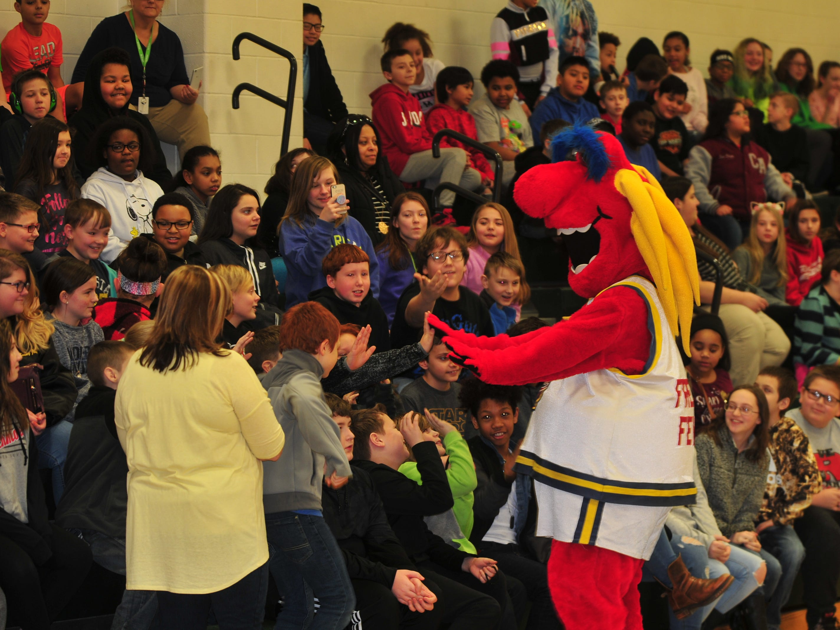 Freddy Fever, mascot for the WNBA's Indiana Fever entertains Dennis Intermediate School students Wednesday.