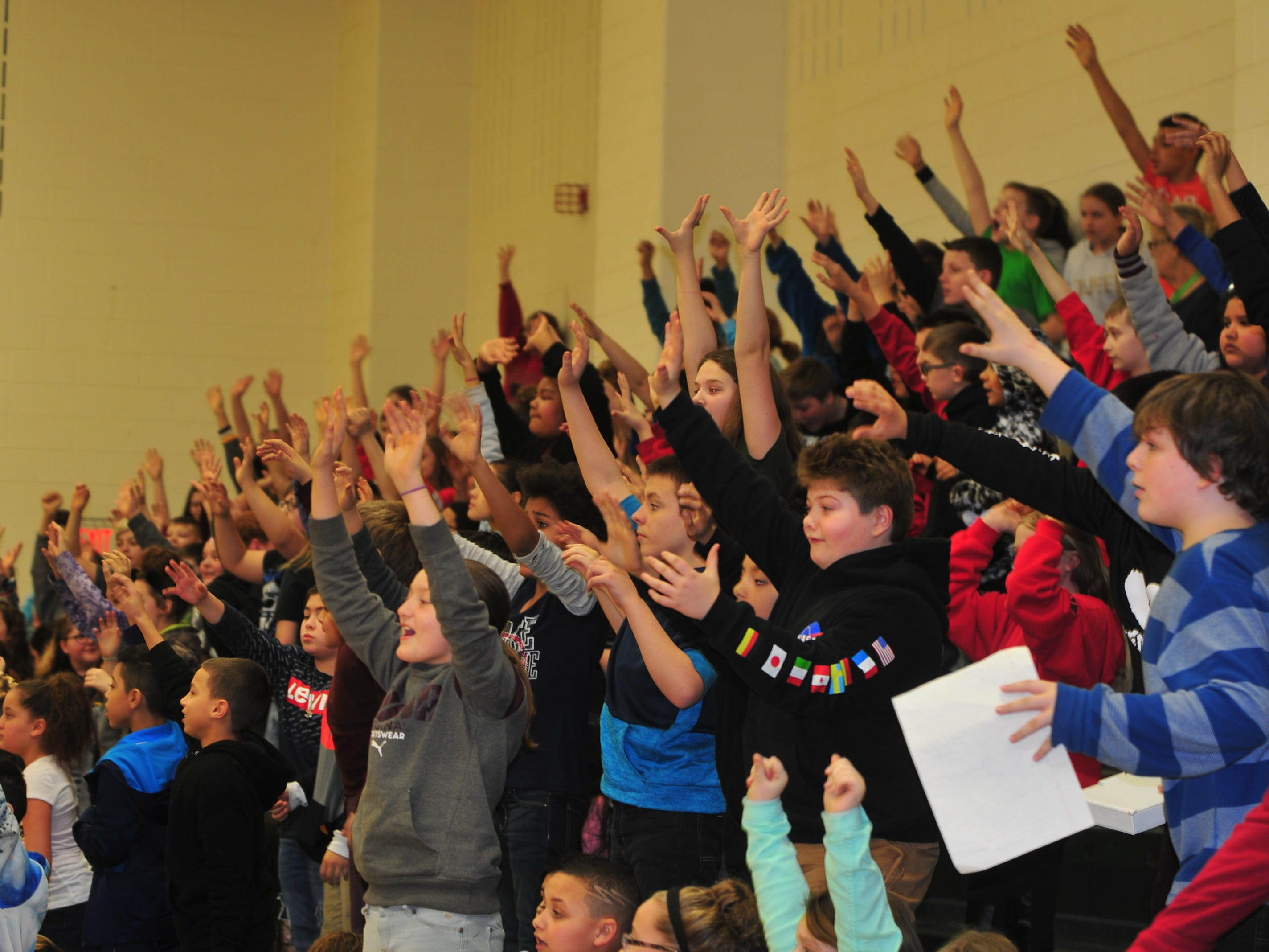 Dennis Intermediate School students raise their hands as T-shirts are tossed into the stands Wednesday.