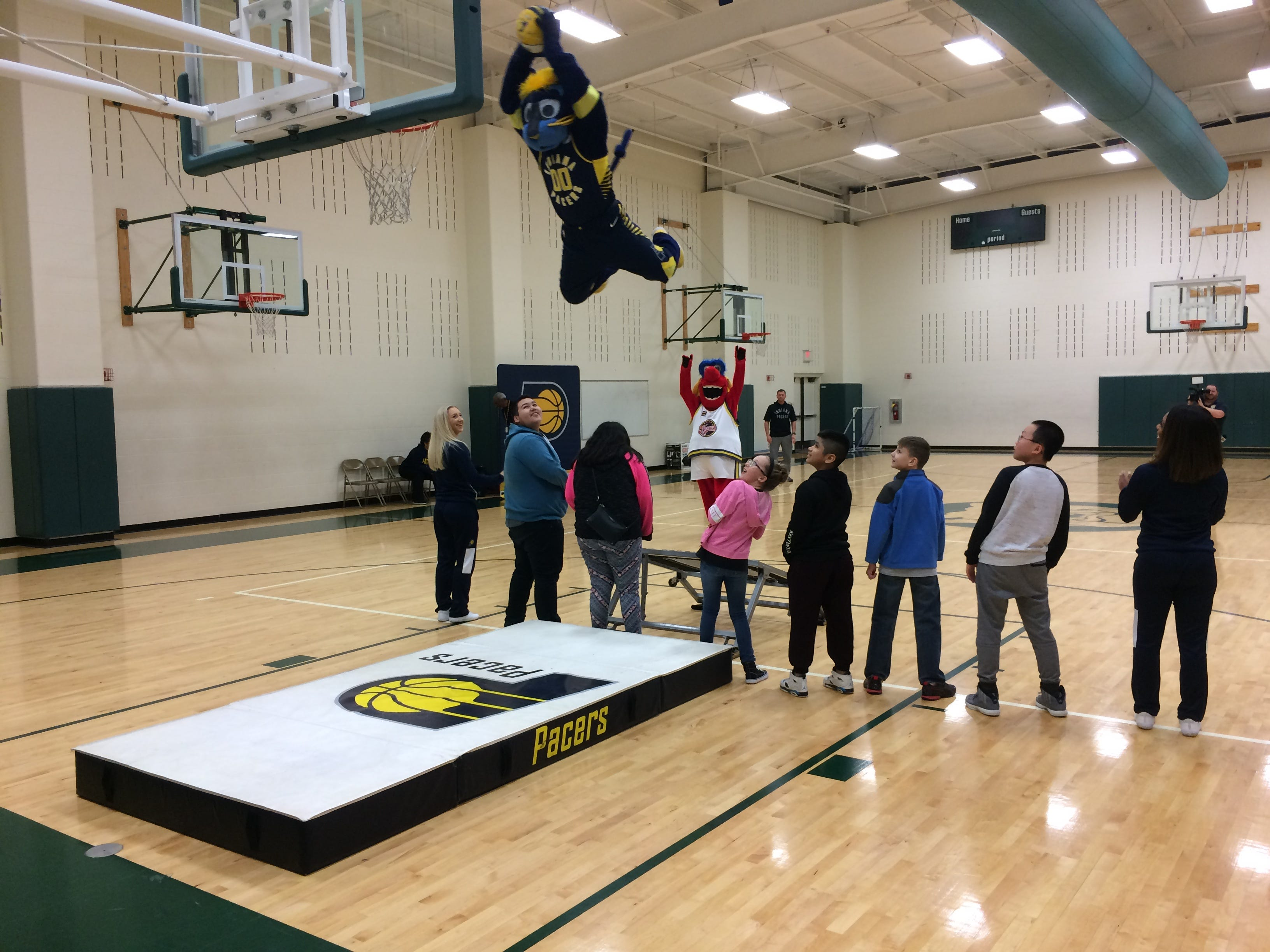Boomer soars over Dennis Intermediate School students to dunk during Wednesday's program.