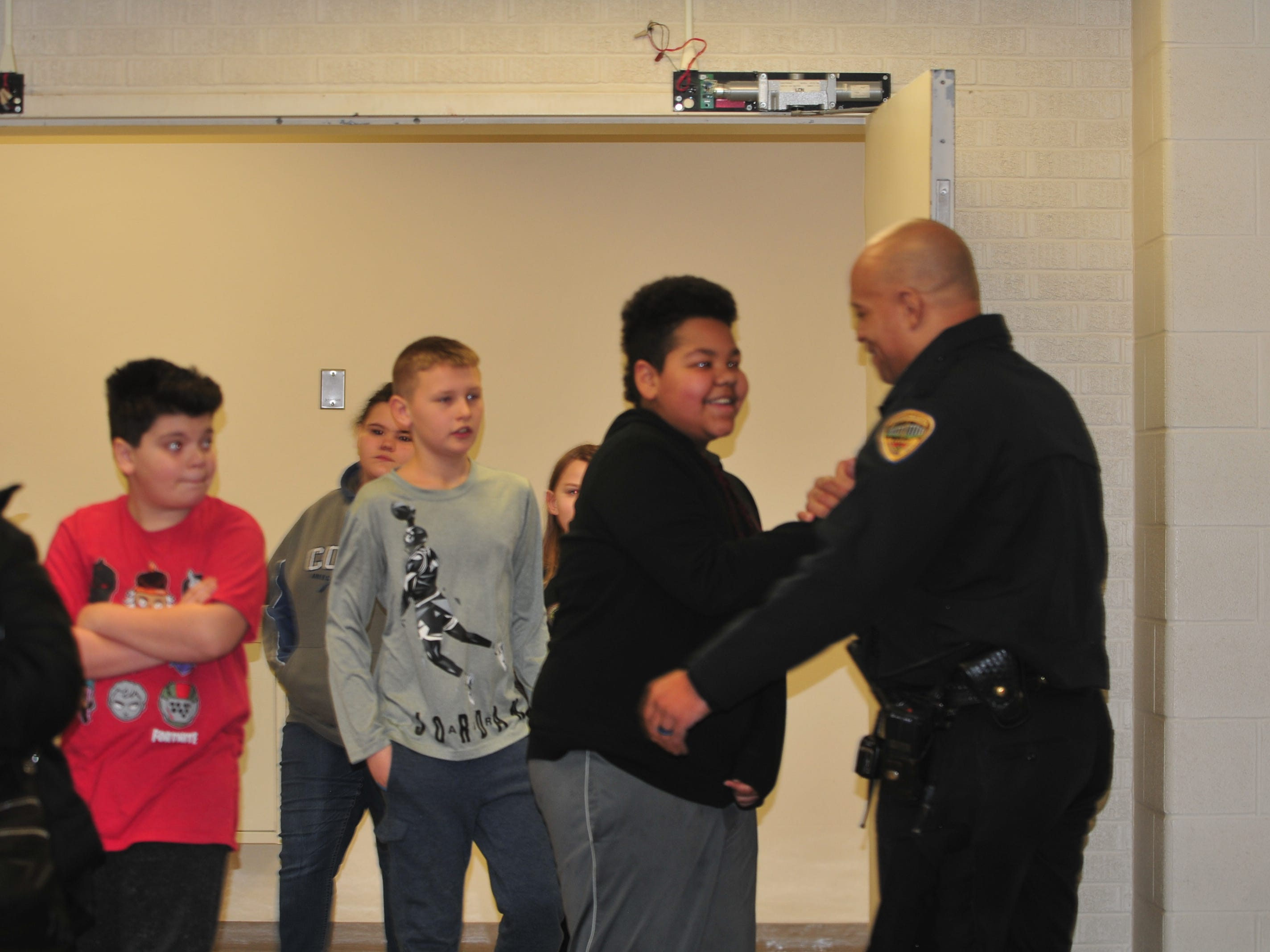 Officer Tim Davis greets students as they file into the gym Wednesday.