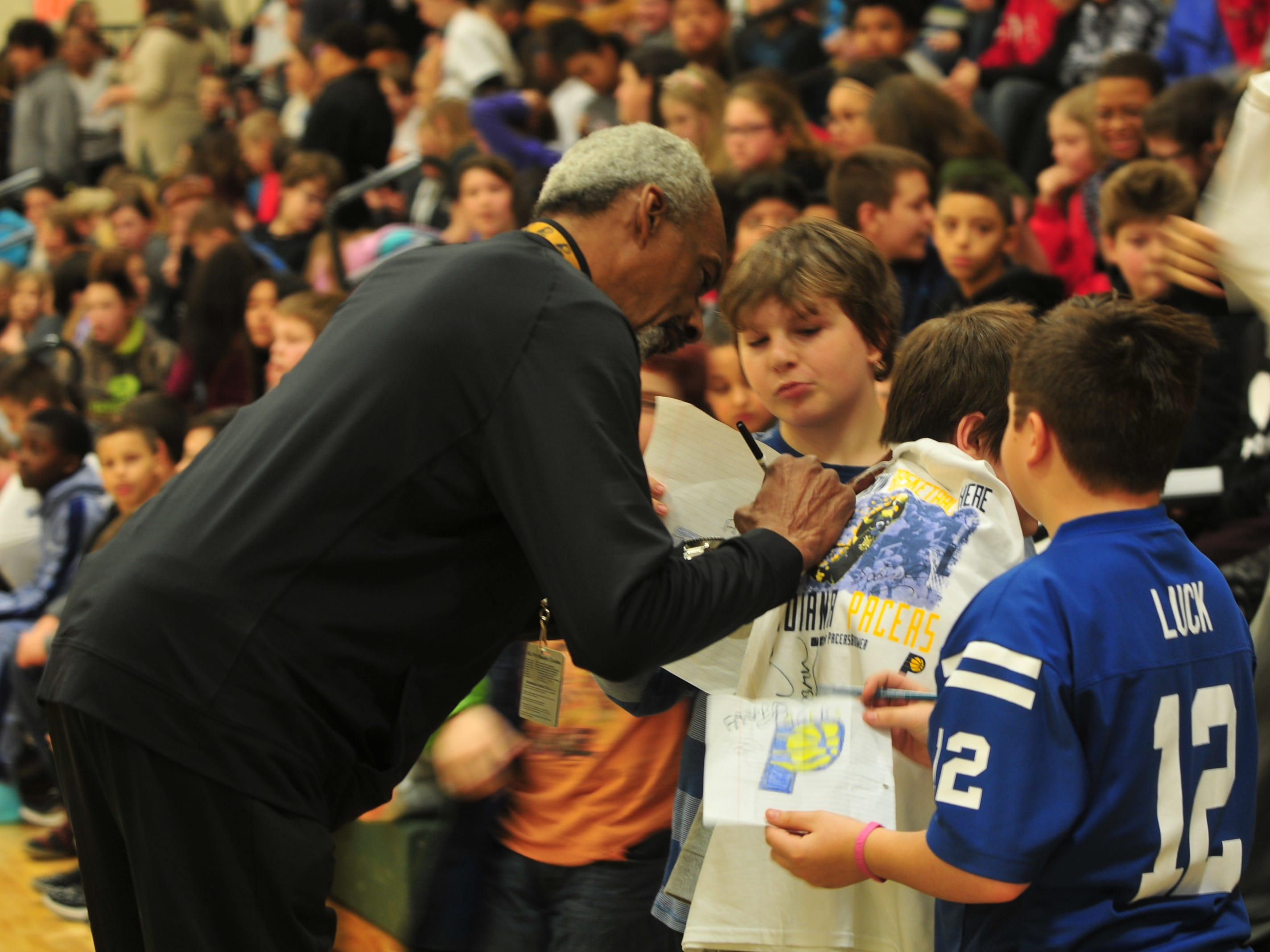 Former Indiana Pacers player Darnell Hillman autographs a T-shirt Wednesday for a Dennis Intermediate School student.
