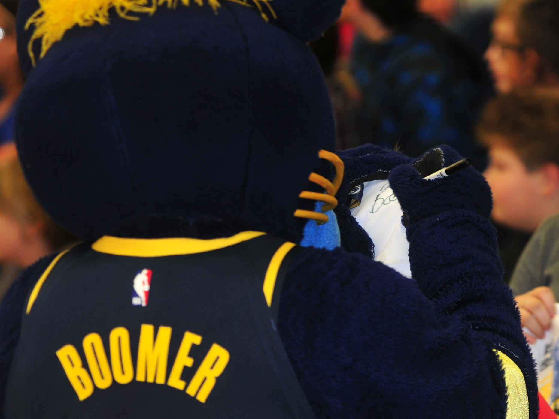 Boomer autographs a T-shirt during Wednesday's program in Dennis Intermediate School.