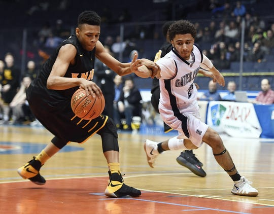 McQuaid's Jermaine Taggart, left, shields the ball from Gates-Chili's Devin Walton during a Class AA sectional semifinal played at the Blue Cross Arena, Tuesday, Feb. 26, 2019. No. 3 seed McQuaid advanced to the Class AA final with a 82-75 win over No. 2 seed Gates-Chili.