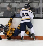 Spencerport's AJ Giannavola is checked to the ice by Thomas's Reed Currie in the Class B final.
