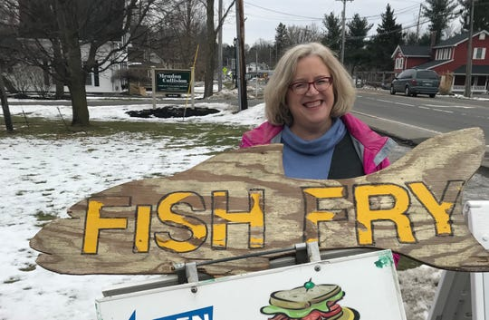 Tracy Schuhmacher poses near a sign for fish fry.