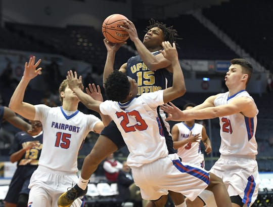 University Prep's Jakhi Lewis, top, drives to the basket while defended by Fairport's Vanzell Johnson (23) and Ryan Lucey during a Class AA sectional semifinal played at the Blue Cross Arena, Tuesday, Feb. 26, 2019. No. 8 seed University Prep advanced to the Class AA final with a 54-43 win over No. 4 seed Fairport.