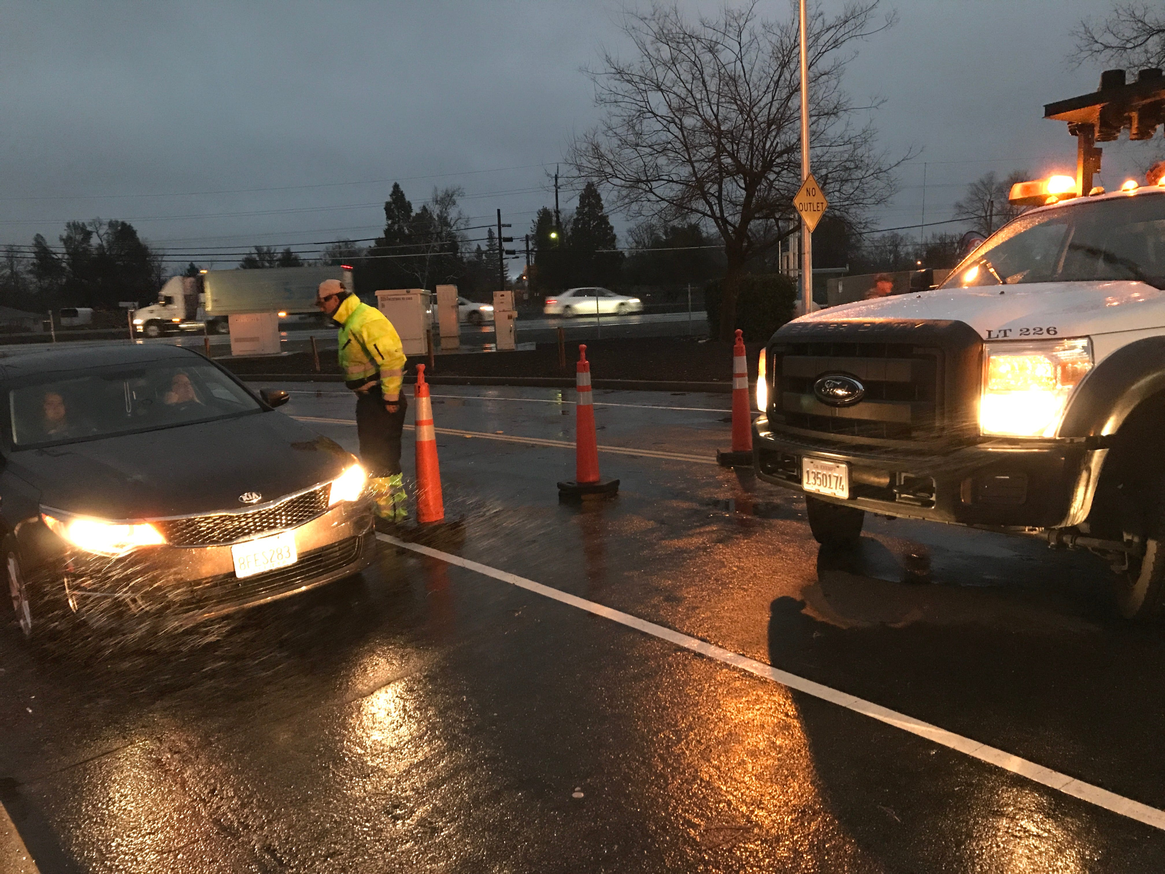 Dave Schultz of Redding's Streets Department checks with a driver Wednesday morning, Feb. 27, 2019, at a roadblock on Westside Road due to flooding.