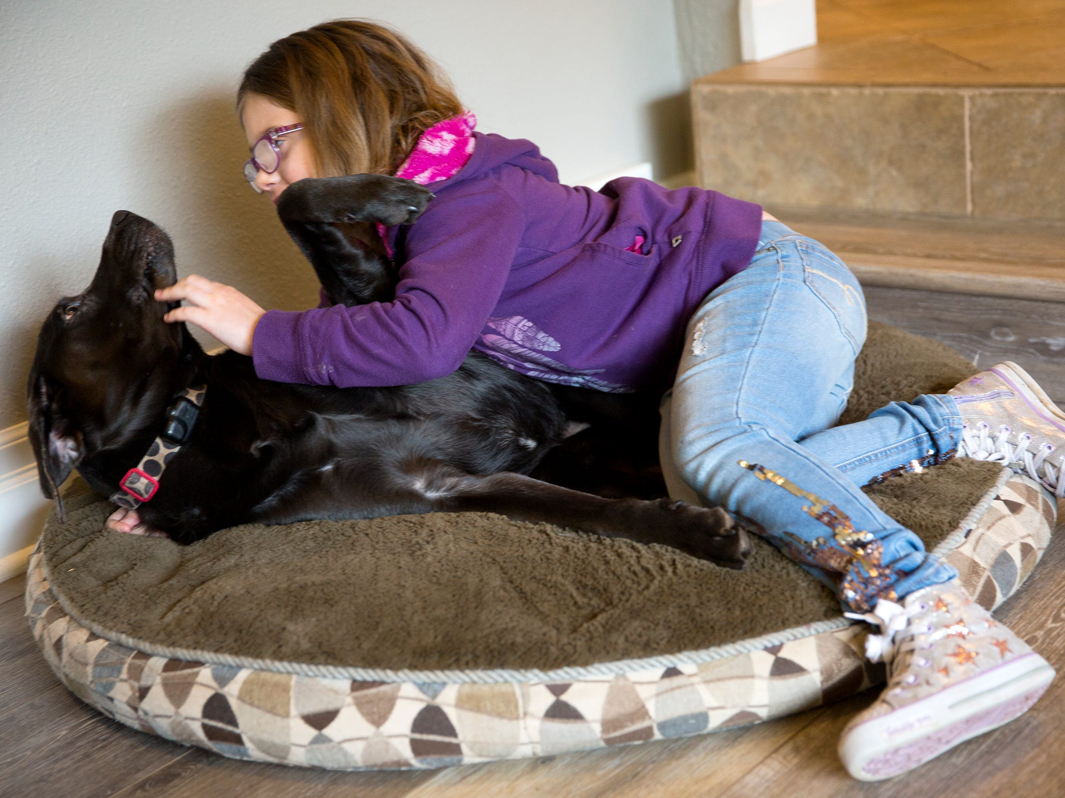 Haley Pollman, 9, plays with her dog Lucy at her home in Salem on Saturday, Feb. 23, 2019.