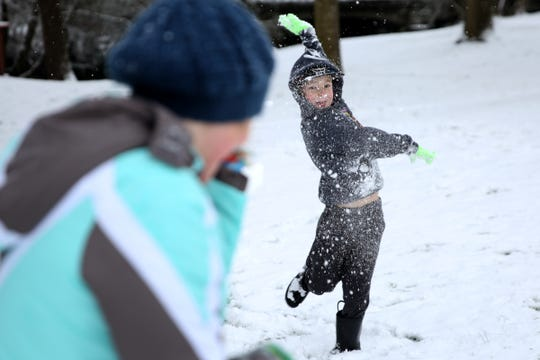 Spencer Maxwell, 7, throws a snowball at his sister Miley Maxwell, 11, of Salem, as snow falls in Salem on Wednesday, Feb. 27, 2019.