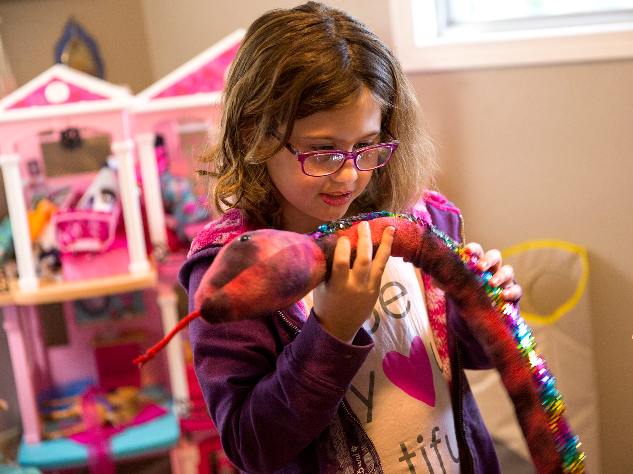 Haley Pollman, 9, looks into the reflection of her toy snake at her home in Salem on Saturday, Feb. 23, 2019. She has a rare nervous system disorder that has caused her eyesight to deteriorate.