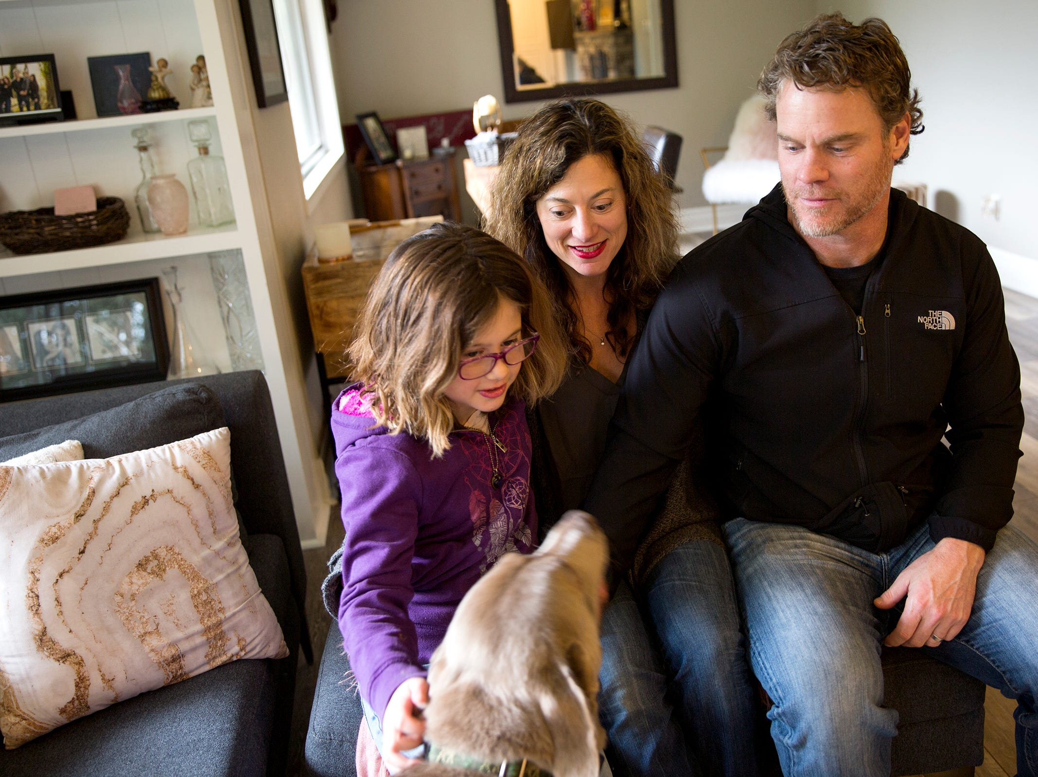 Haley Pollman, 9, and her parents Melissa Pollman and Dean Pollman pet their dog Gary at their home in Salem on Saturday, Feb. 23, 2019.