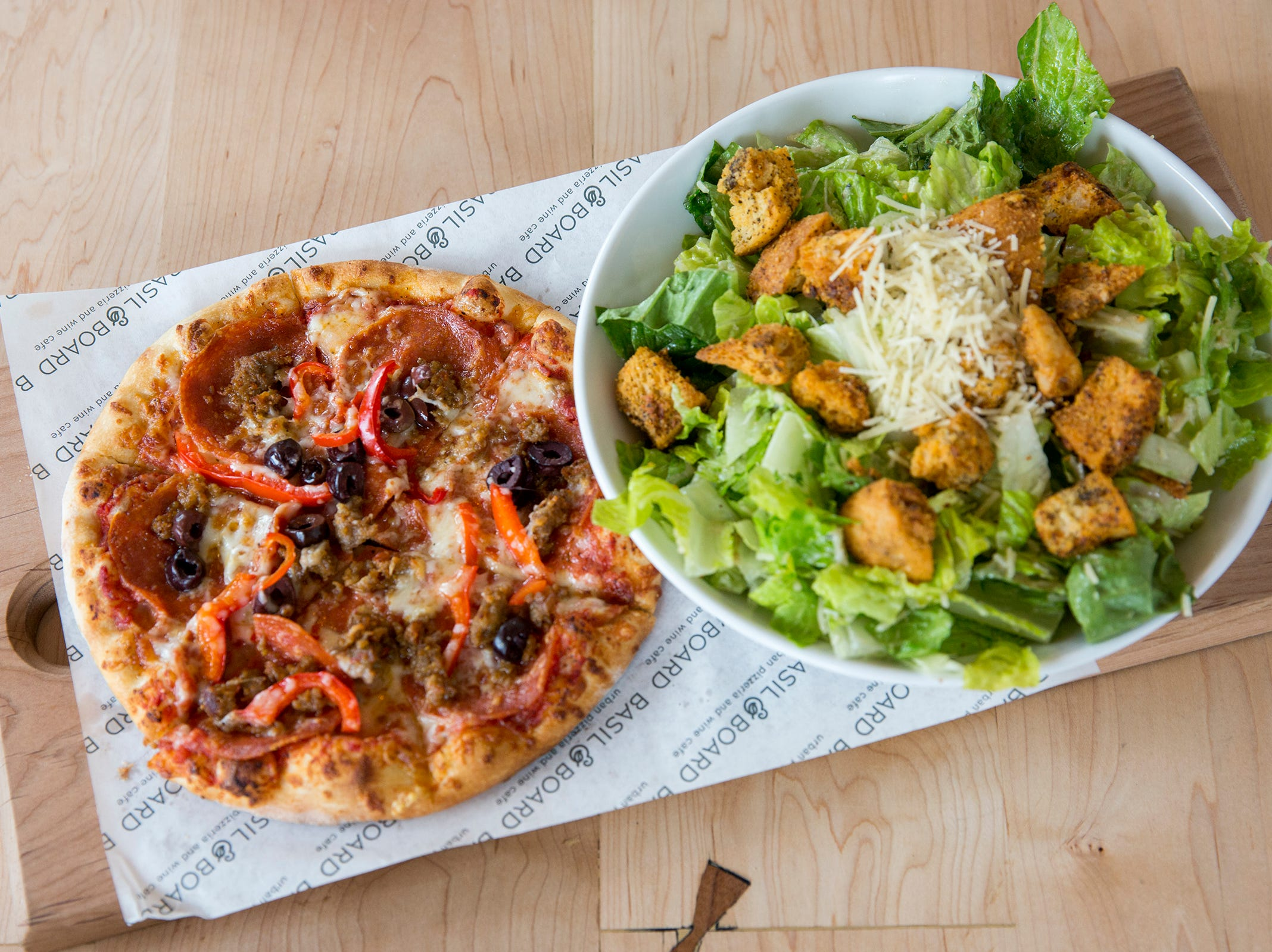 An 8 inch Isle of the Gods pizza from the lunch menu is paired with a salad in Salem on Tuesday, Feb. 26, 2019.