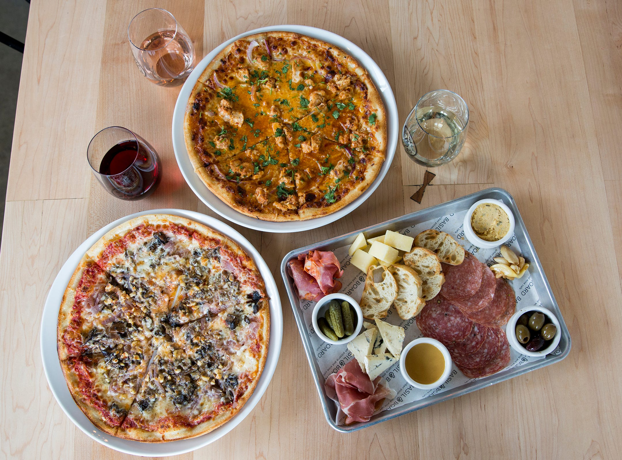 The Pacific Crest Trail pizza, the BBQ Bird pizza and a small butcher's board are pictured with three glasses of wine at Basil & Board in Salem on Tuesday, Feb. 26, 2019.