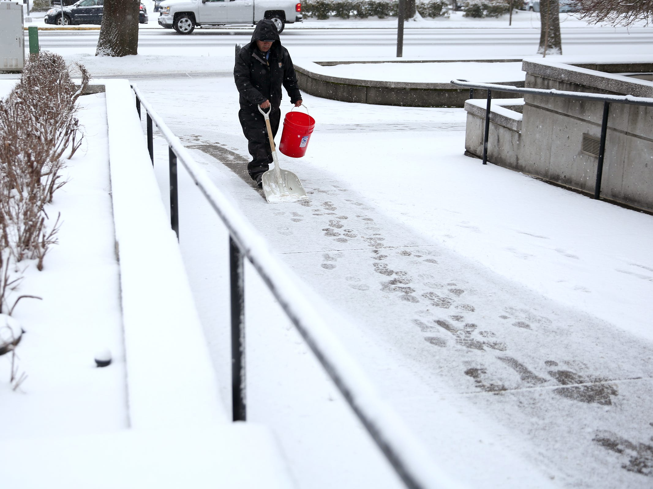 Domingo Hildalgo, a maintenance worker with the State of Oregon, shovels a walkway outside the Oregon Department of Human Services office as snow falls in Salem on Wednesday, Feb. 27, 2019.