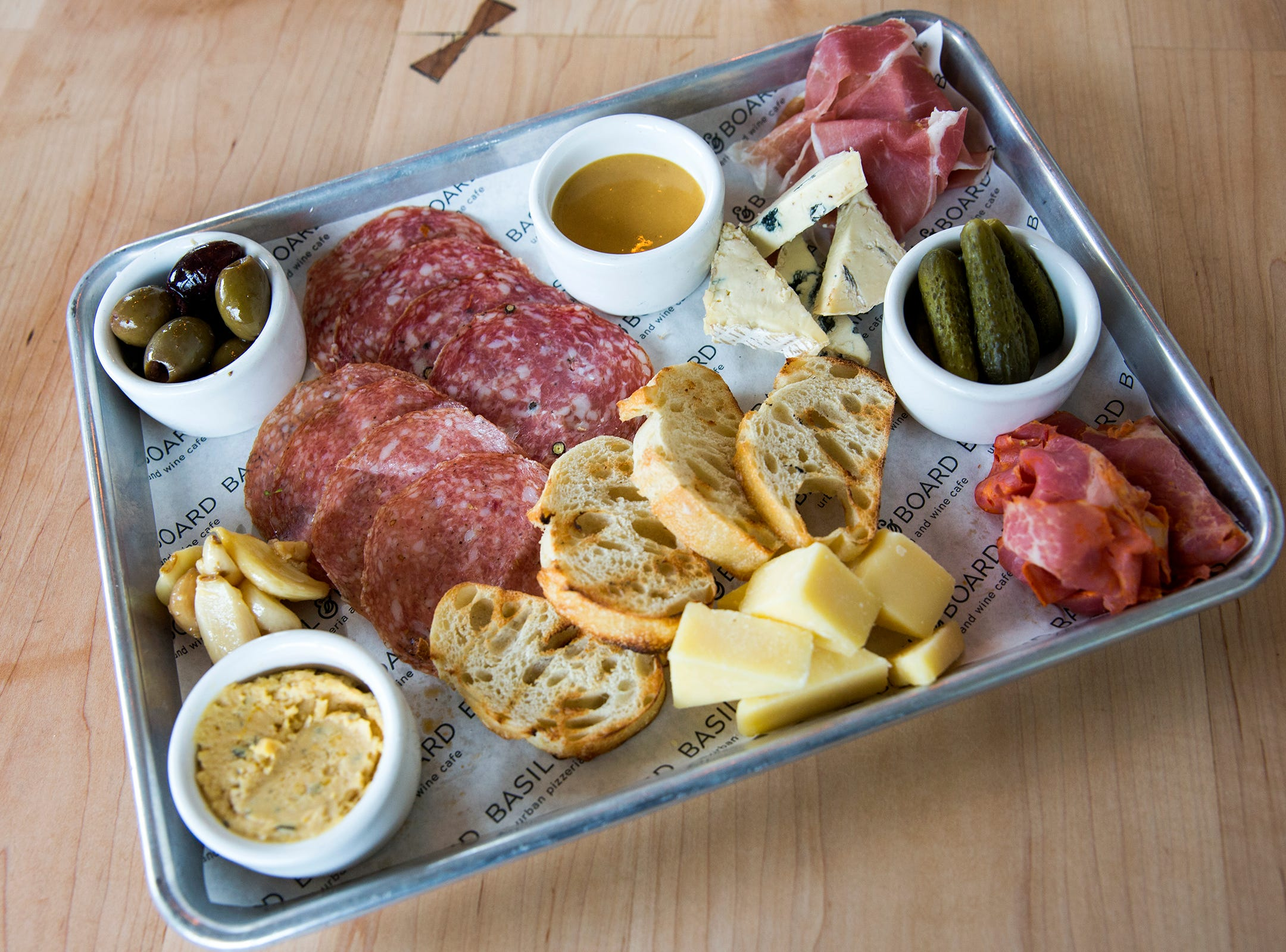 A small Butcher's Board, available during social hours from 3 p.m. to 5 p.m. and 7 p.m. to close, is pictured at Basil & Board in Salem on Tuesday, Feb. 26, 2019. The board includes a variety of craft meats and cheeses paired with rosemary hummus and greek olives.