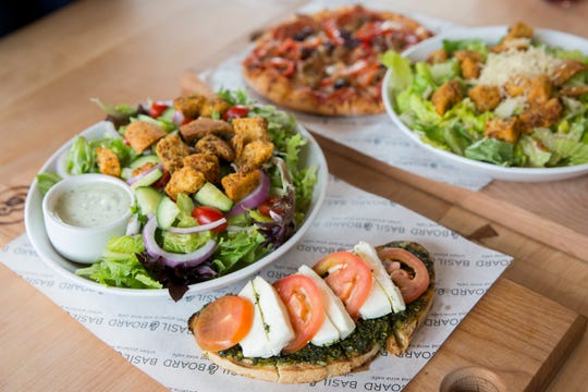 The 1948 bruschetta, which has pepita pesto, fresh mozzarella and tomatoes, is paired with a salad on the lunch menu at Basil & Board in Salem on Tuesday, Feb. 26, 2019.