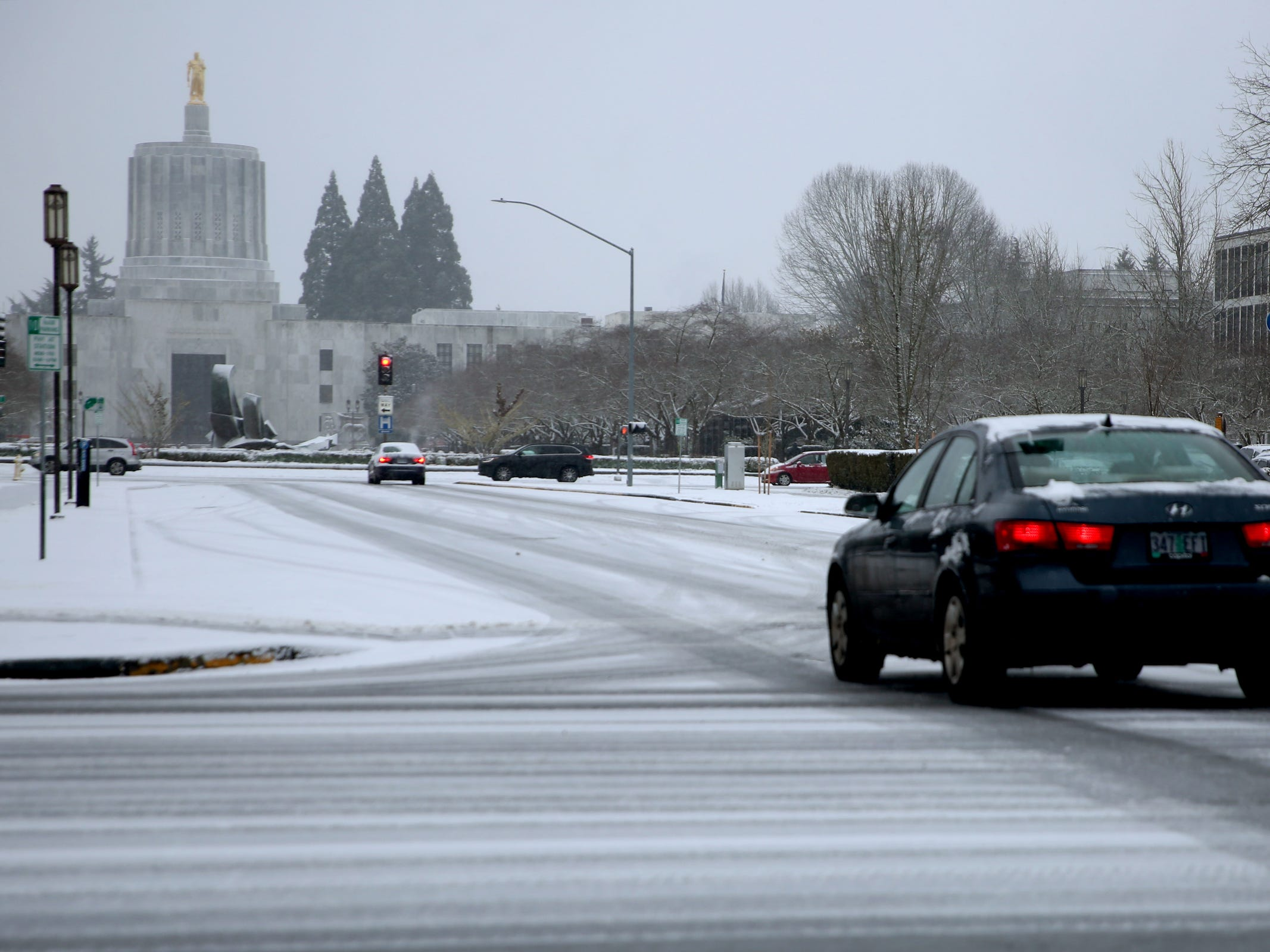 A car drives near the Oregon State Capitol as snow falls in Salem on Wednesday, Feb. 27, 2019.