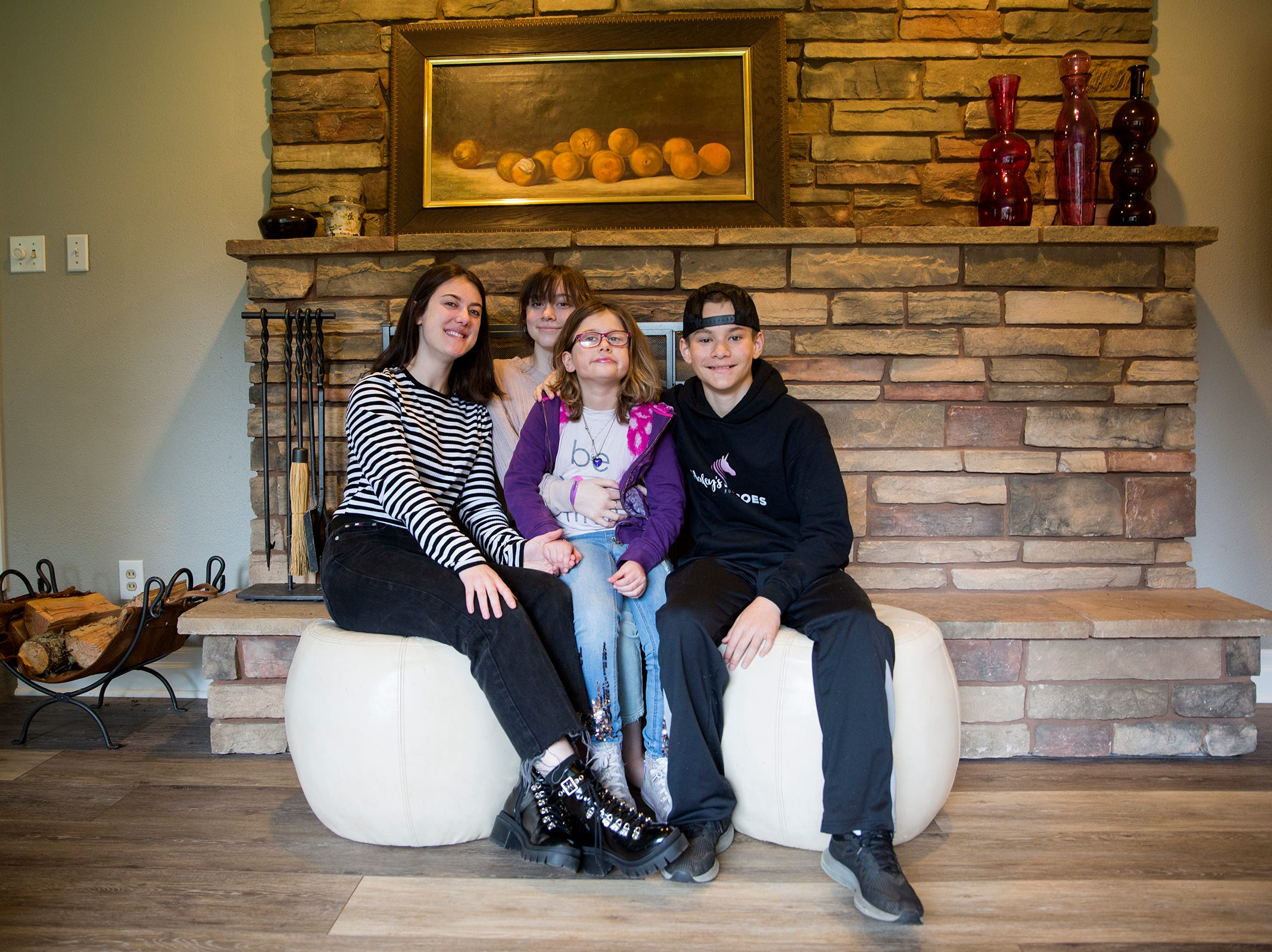 Haley Pollman, 9, (center) and her siblings Audrey, 21, Maddie, 15, and Cole, 11 pose for a photo at their home in Salem on Saturday, Feb. 23, 2019.