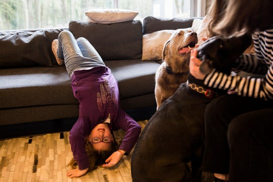 Haley Pollman hangs upside down on her living room couch while her older sister plays with their dogs at their home in Salem on Saturday, Feb. 23, 2019.