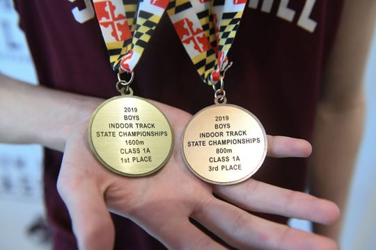 Keegan Gould holds his medals for winning 1st place in the 1600 meter race and 3rd in the 800m race.