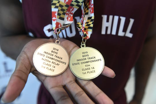 Charles Townsend II holds his medals for winning 1st place in the 55m race and 3rd 4x200m Relay.