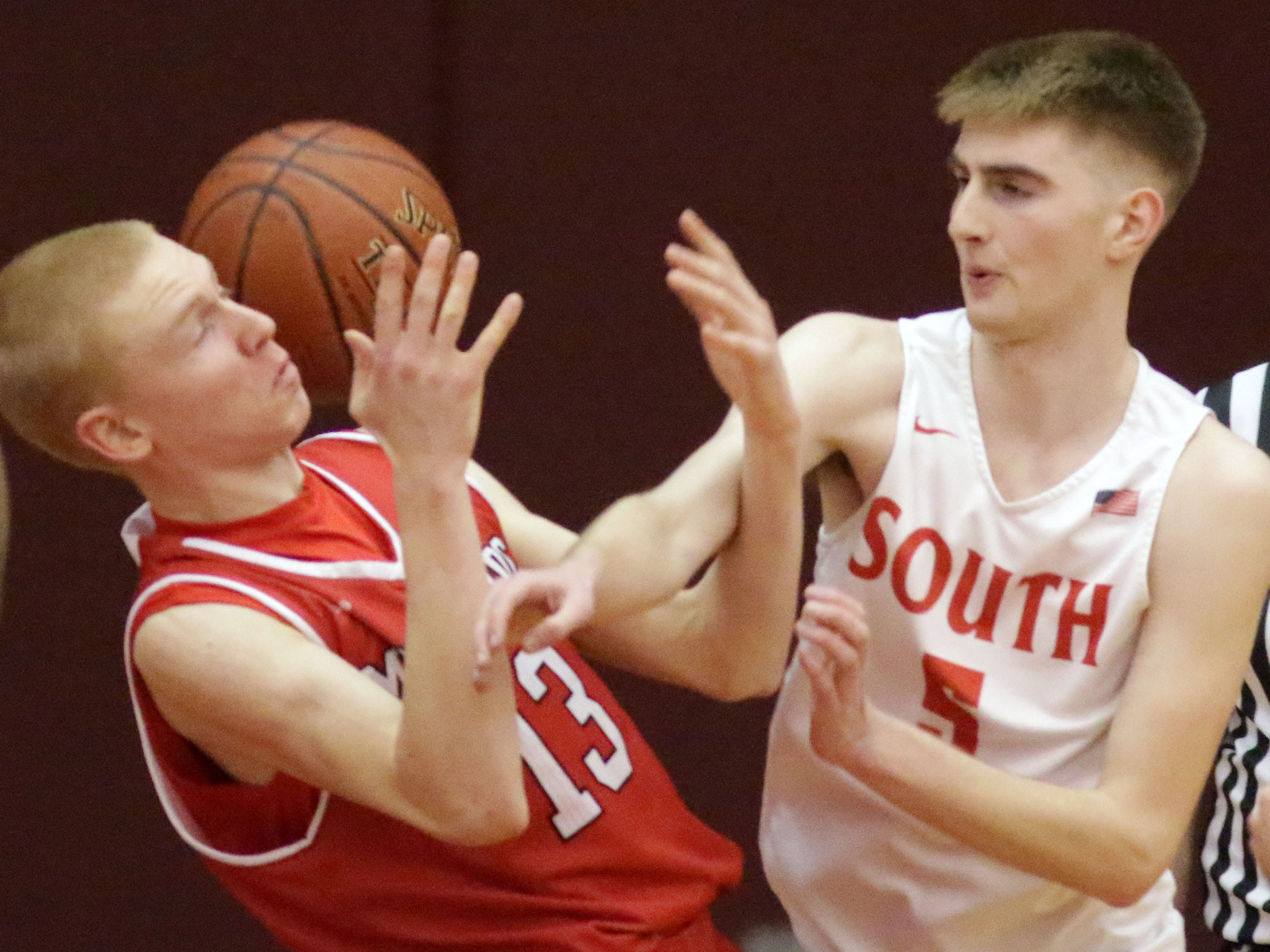 Manitowoc Lincoln's Sam Jacobson (13) and Sheboygan South's Jake Marver (5) bobble the ball, Tuesday, February 26, 2019, in Sheboygan, Wis.